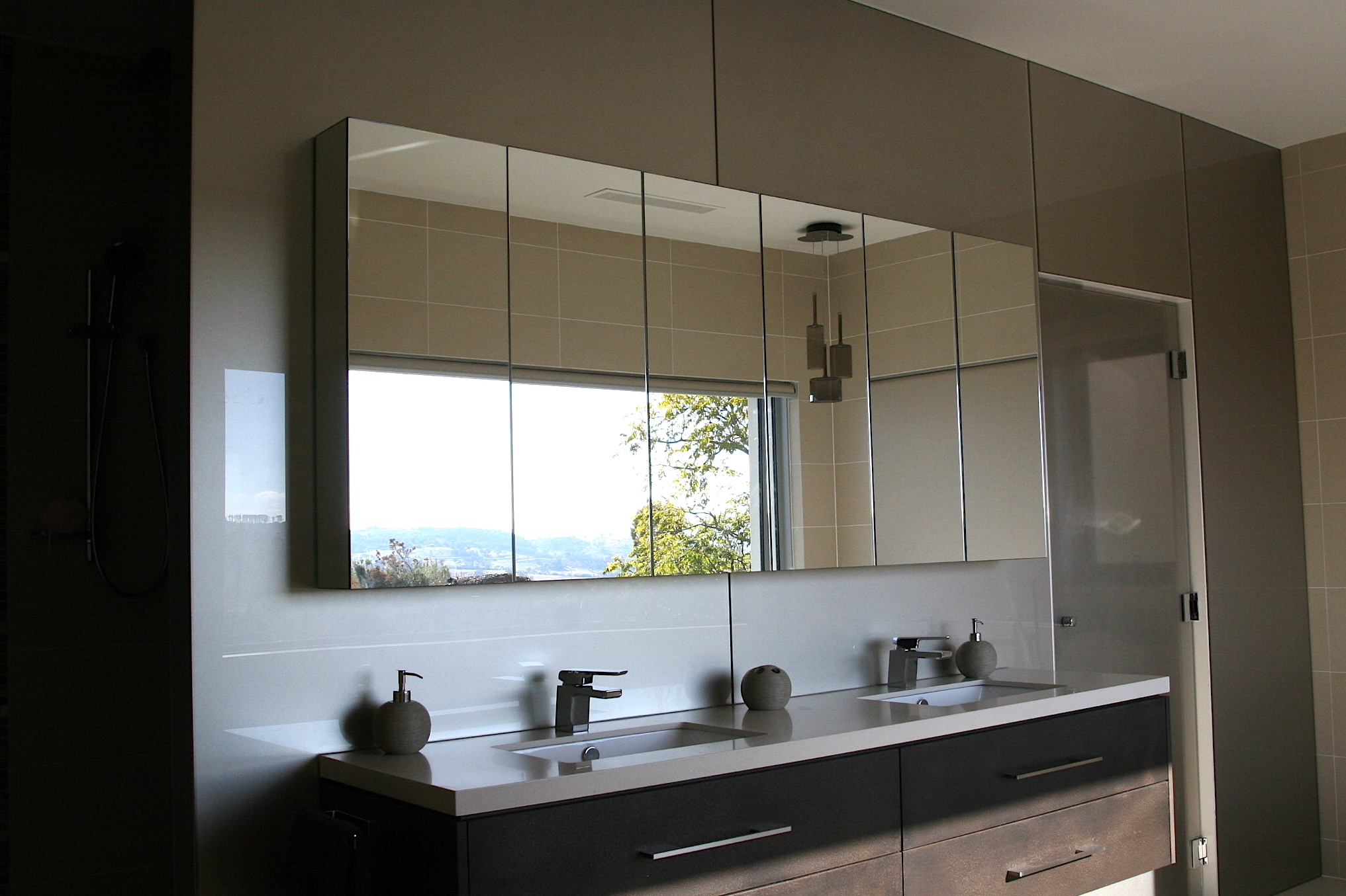 Custom made silver mirrors on front of bathroom cabinetry.