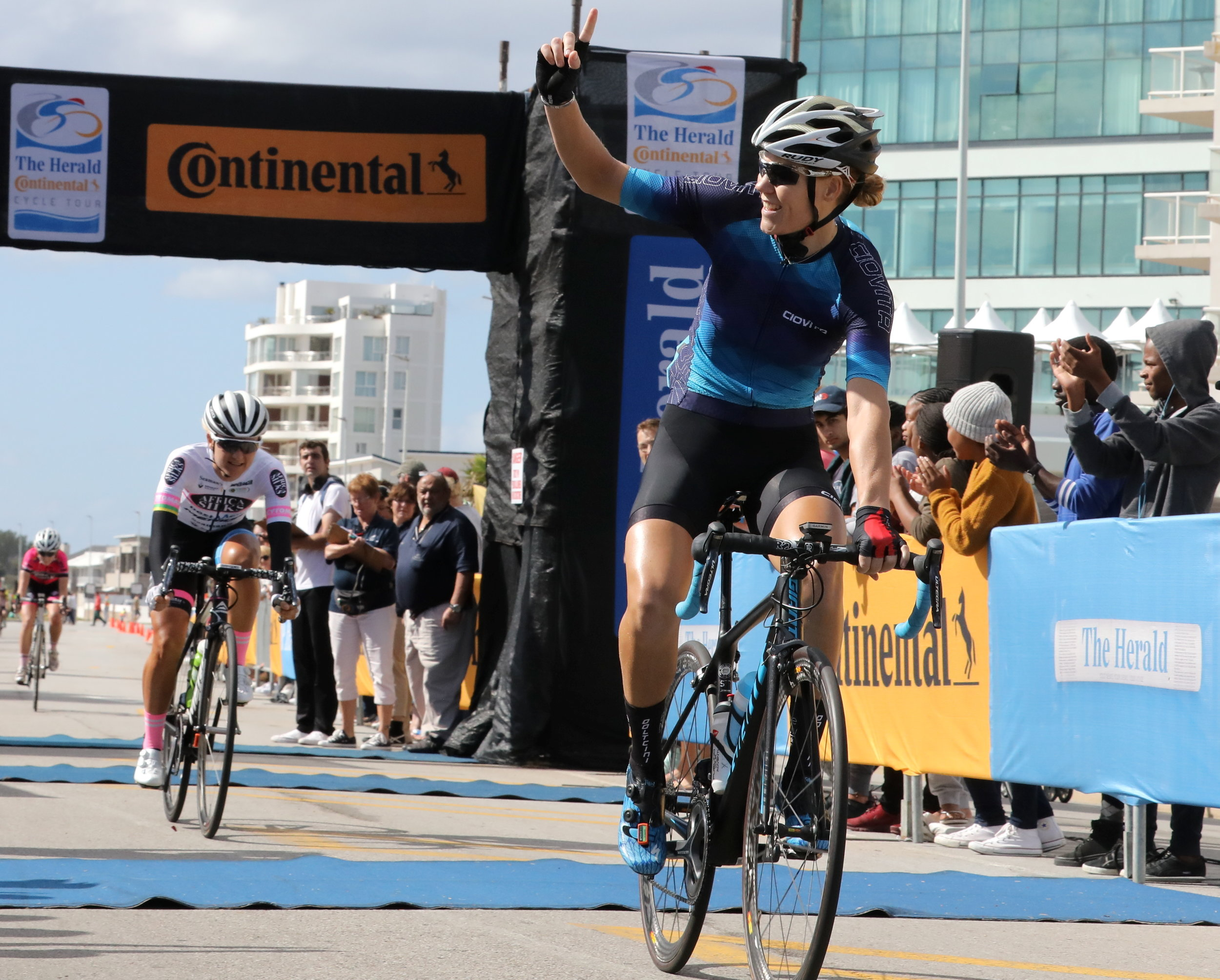 WOMAN POWER: The Herald Continental Cycle Tour women's winner Maroesjka Matthee, of Cape Town, salutes the crowd as she crosses the finish line ahead of Port Elizabeth's racing queen Anriette Schoeman close behind Picture: FREDLIN ADRIAAN