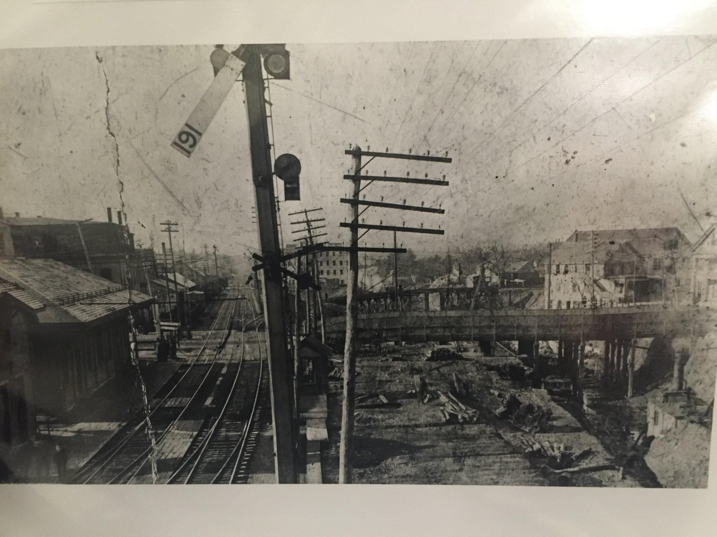 The original (1850s) Natick station building is on the left, and excavations to lower the tracks have begun on the right.