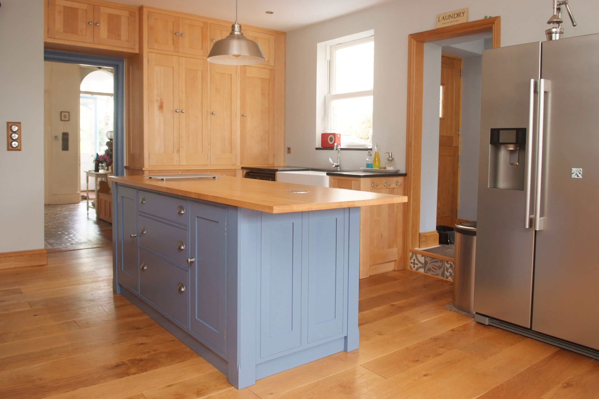 This kitchen is built in maple and has a central island with painted units and a maple worktop