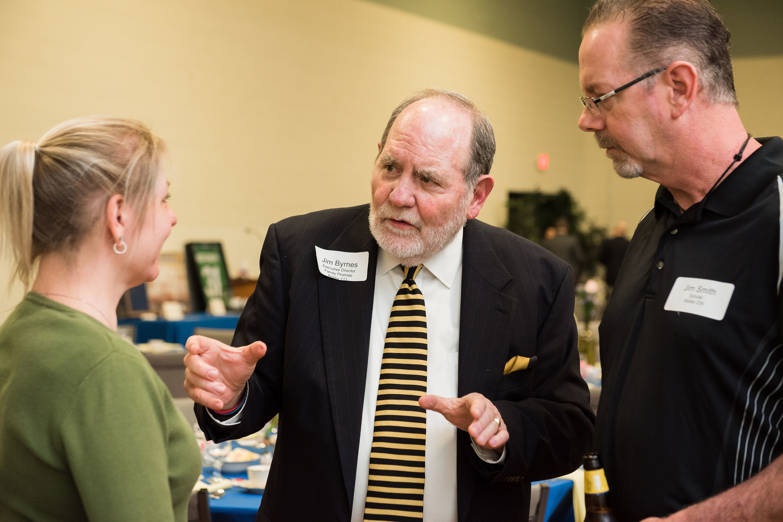Jim Byrnes speaking with two guests at the 2019 Family Promise Homecoming Event in March 2019.