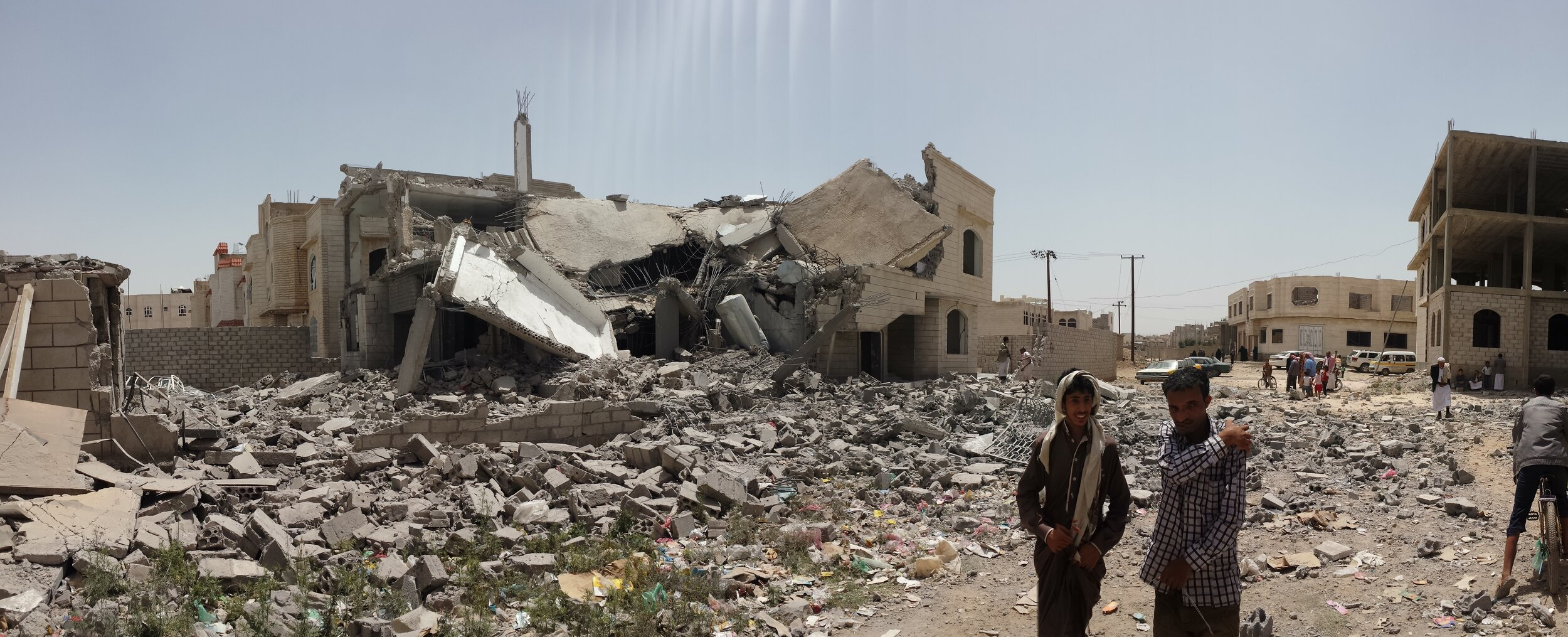 Yemenis stand next to a house destroyed by bombardment in Sana'a, 2016.