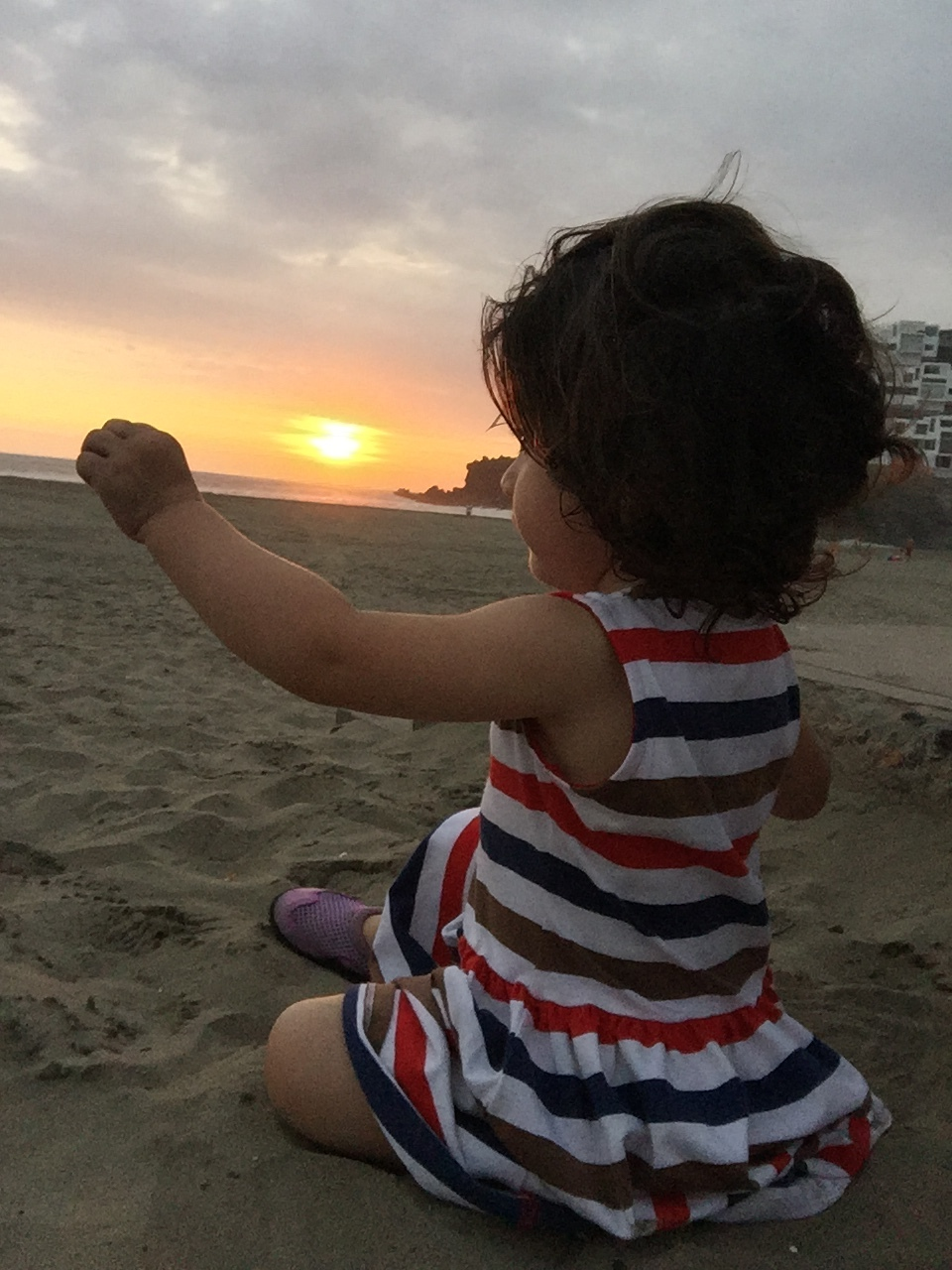 Mia trying to touch the sun at the Santa Maria del Mar beach resort in Lima,  Peru