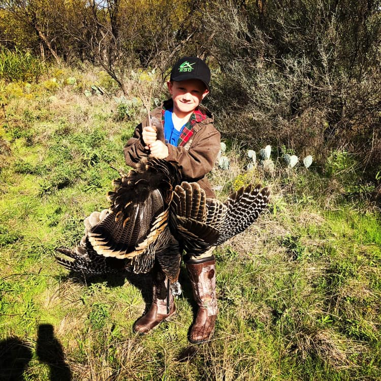 Administrator Chester Barnes' son, Layne holding up his dad's turkey