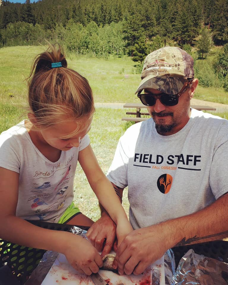 Field Staffer Todd Sellon teaching his daughter how to clean a fish