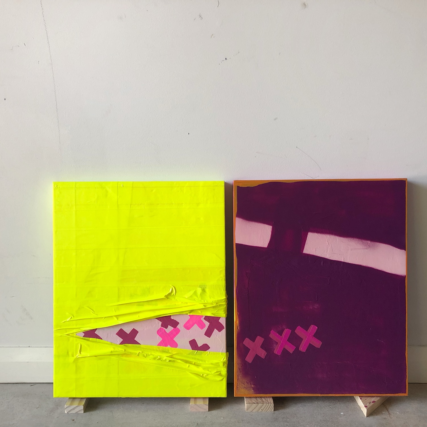 Yellow and purple abstract paintings against white wall