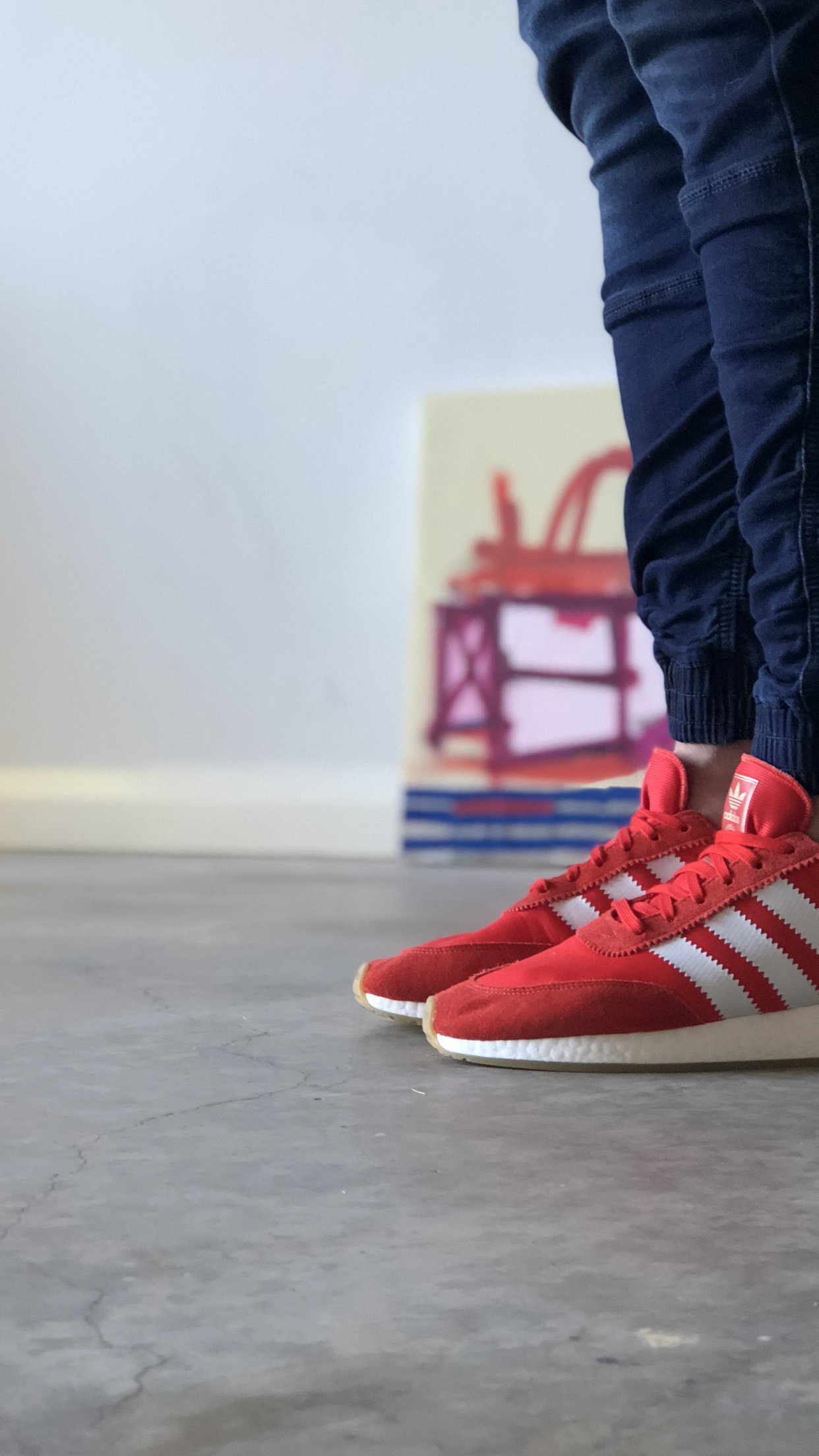 closeup red adidas and man wearing jeans
