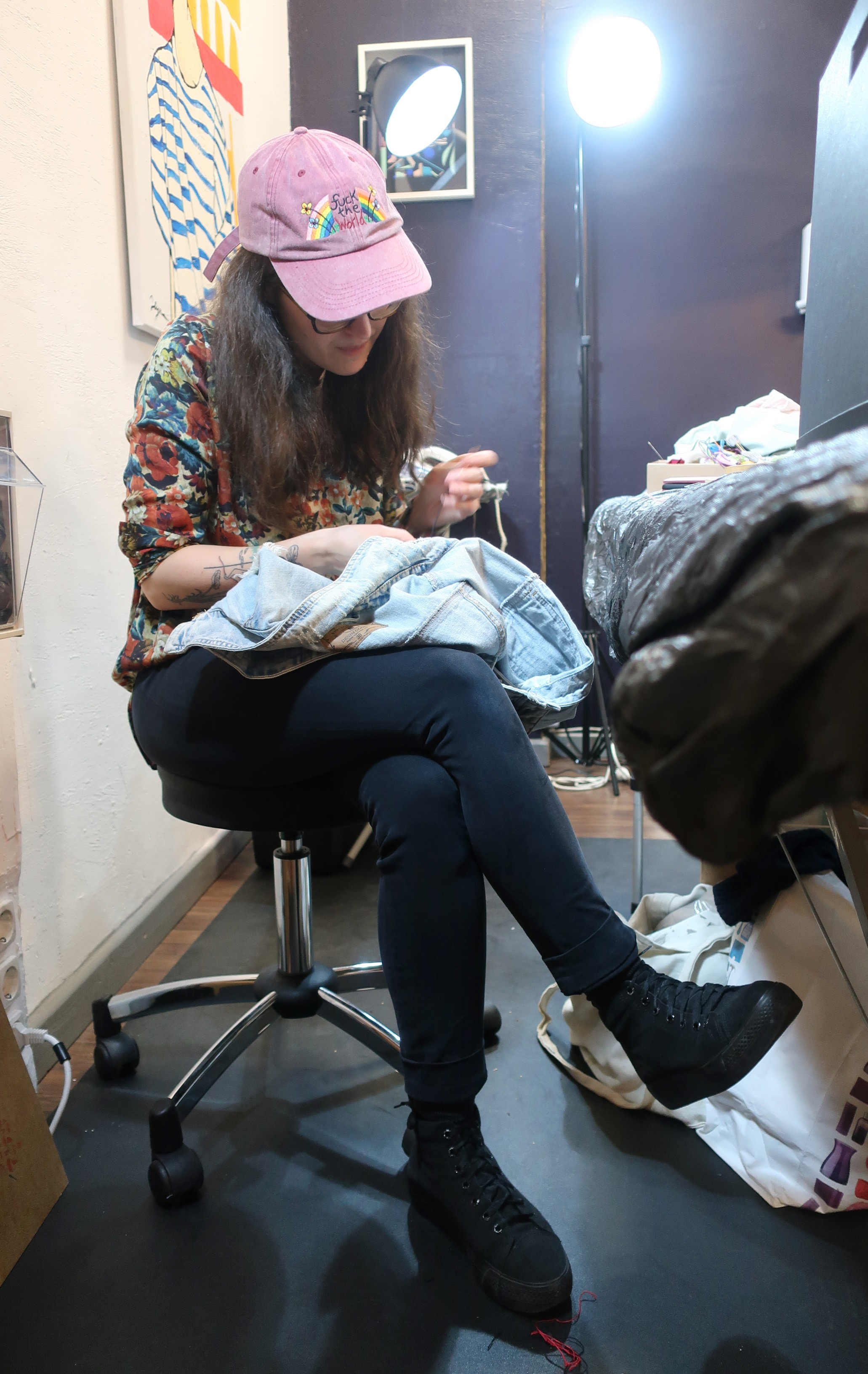 Artist Laura Lesser embroidering denim .jpeg