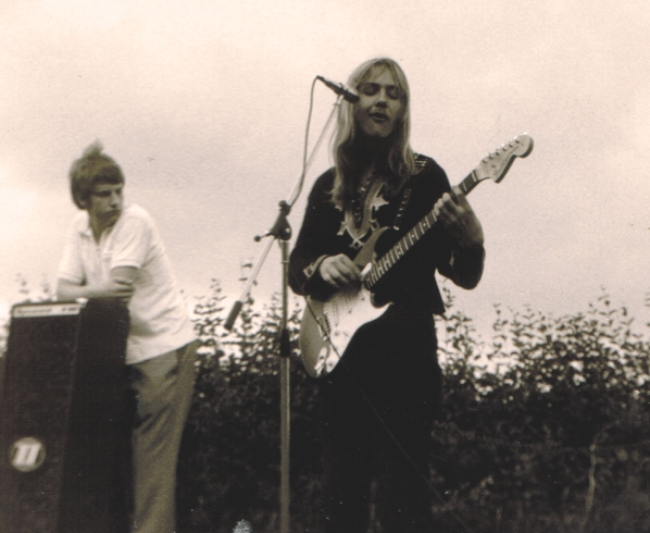 "Uli's 2nd show with his new sunburst Stratocaster guitar.  His then friend and ""manager"", Friedrich (Bantel) Budde watching from the left.  Open air in Hannover, Auf der Bult, 5. June 1971."