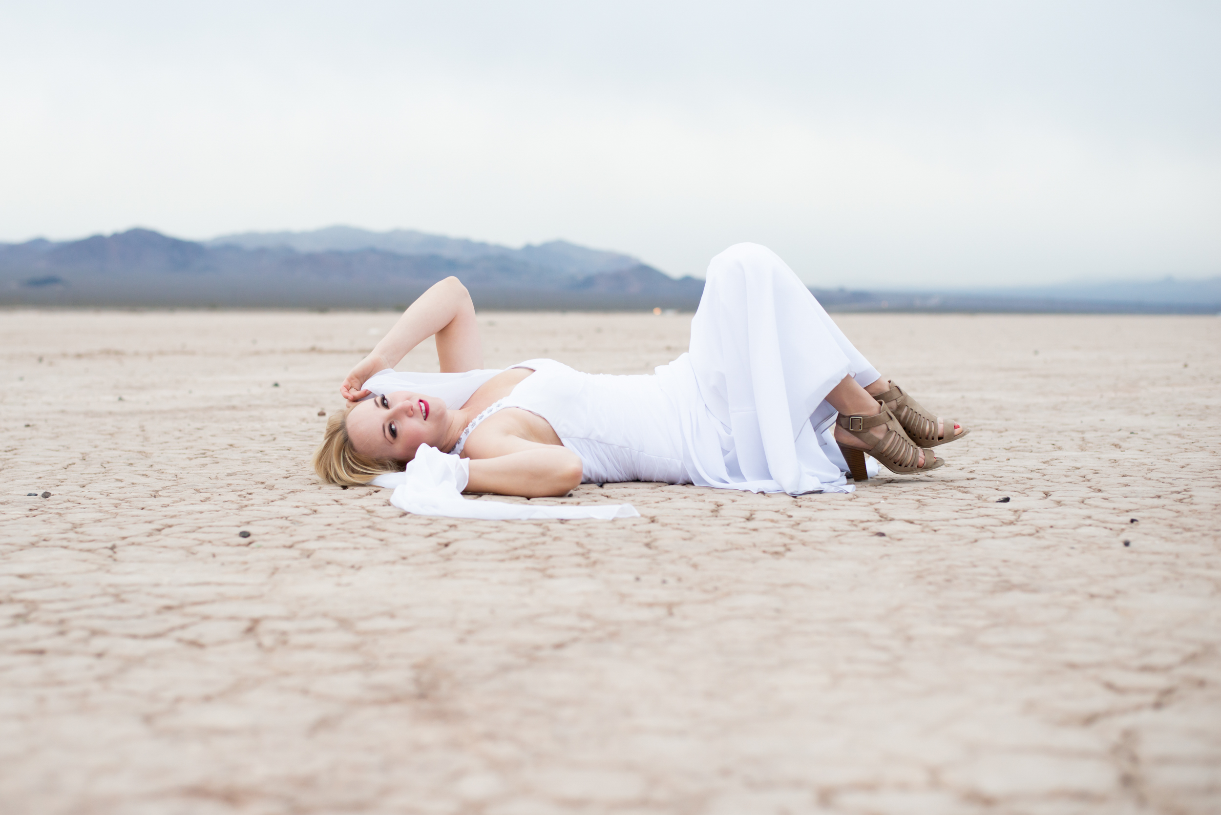 Bride posing in lake bed.