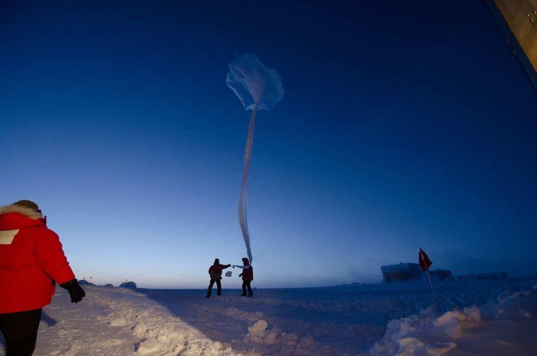 Scientists attach ozone probe to a balloon.