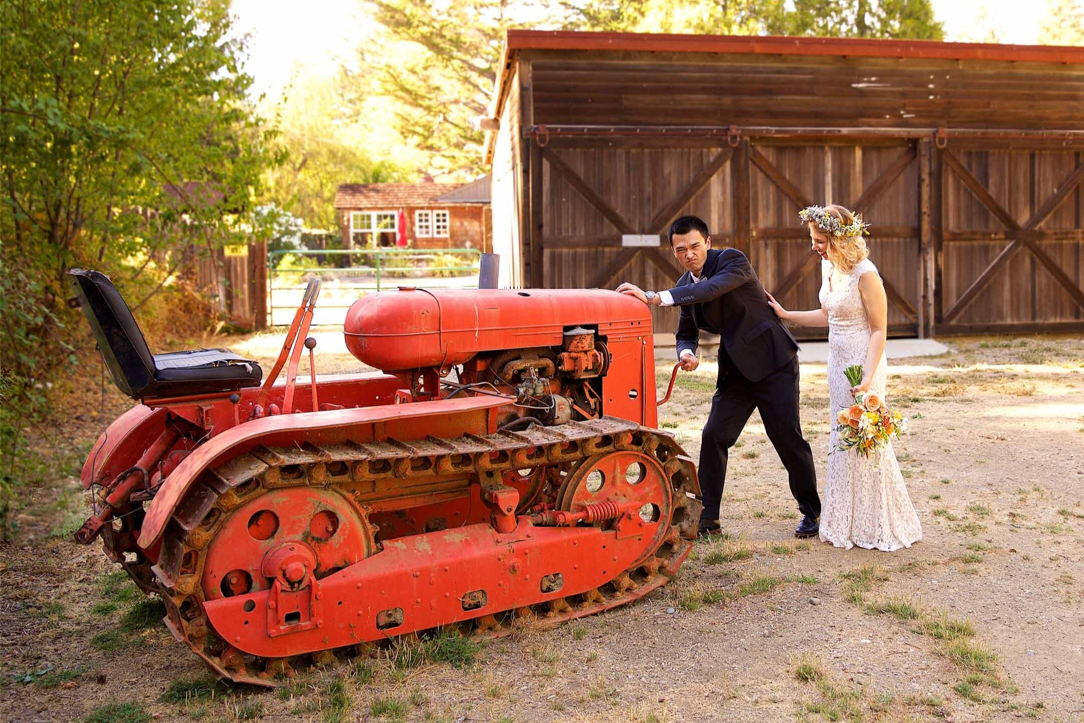 bride-and-groom-standing-next-to-red-tractor-during-their-california-ranch-wedding.jpg