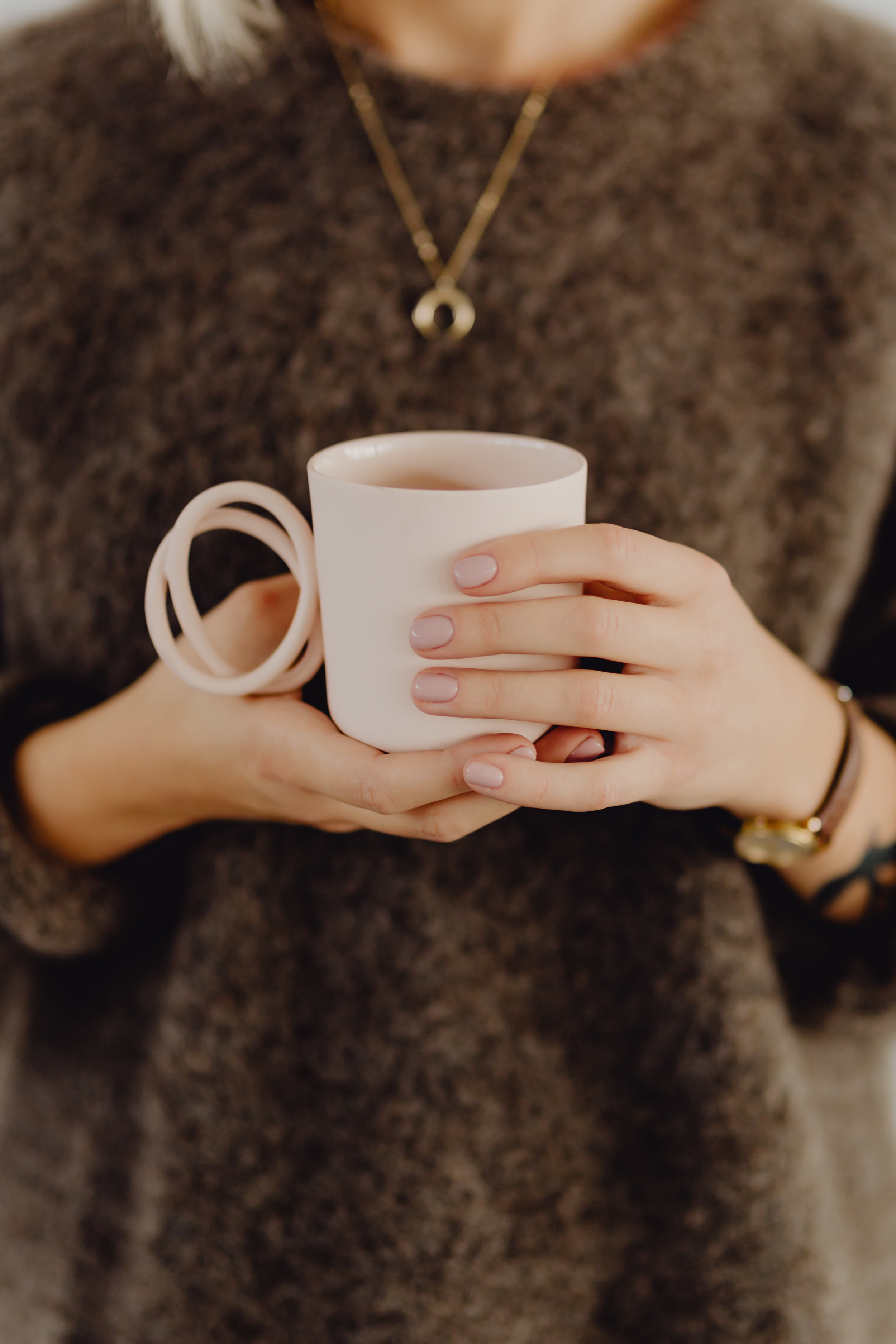 kaboompics_A woman in a brown sweater holds a pink, minimalist mug.jpg