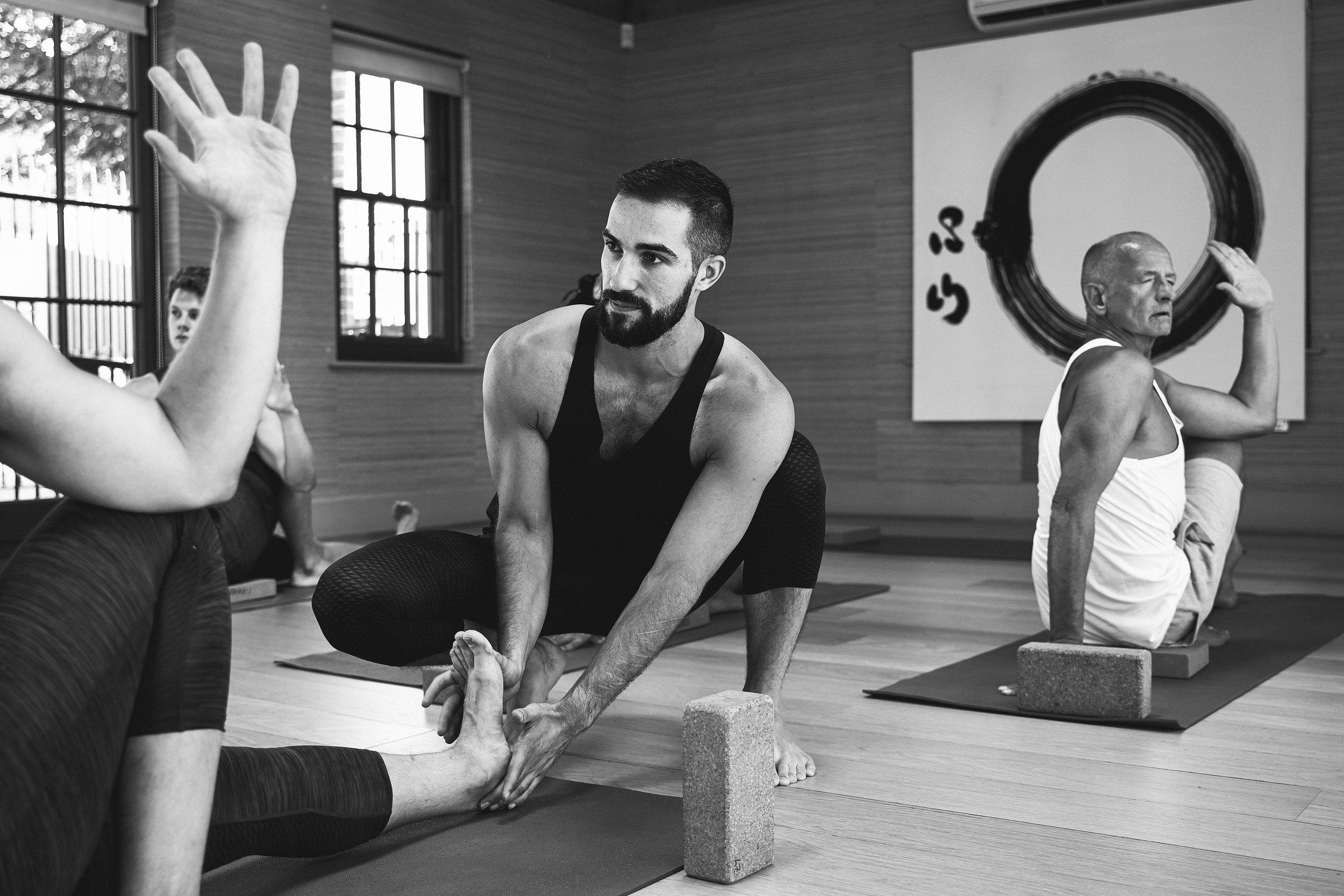 Yoga for men. Men's yoga instructor teaching a group of male yogis