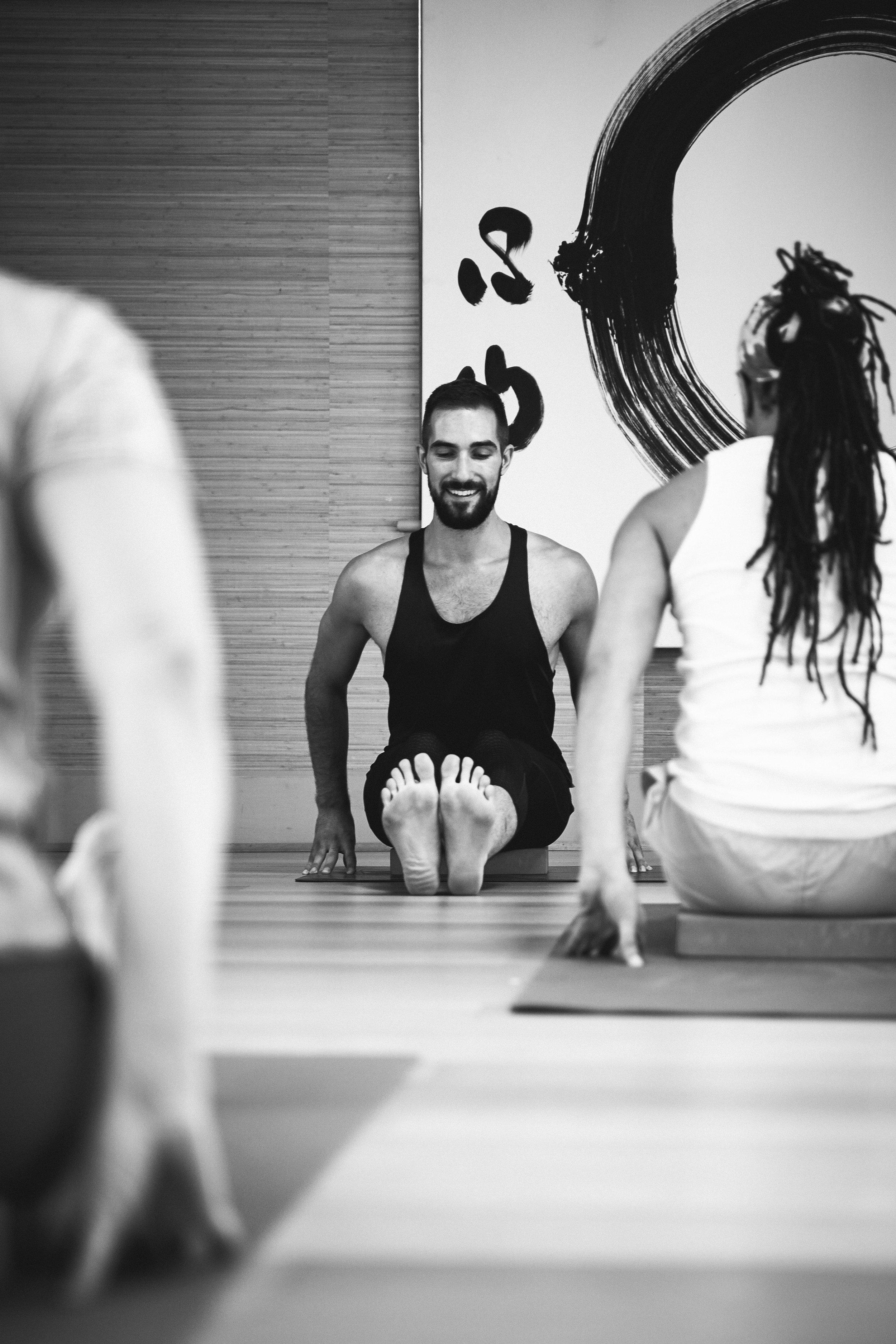 Yoga for men. male yoga teacher doing dandasana forward fold