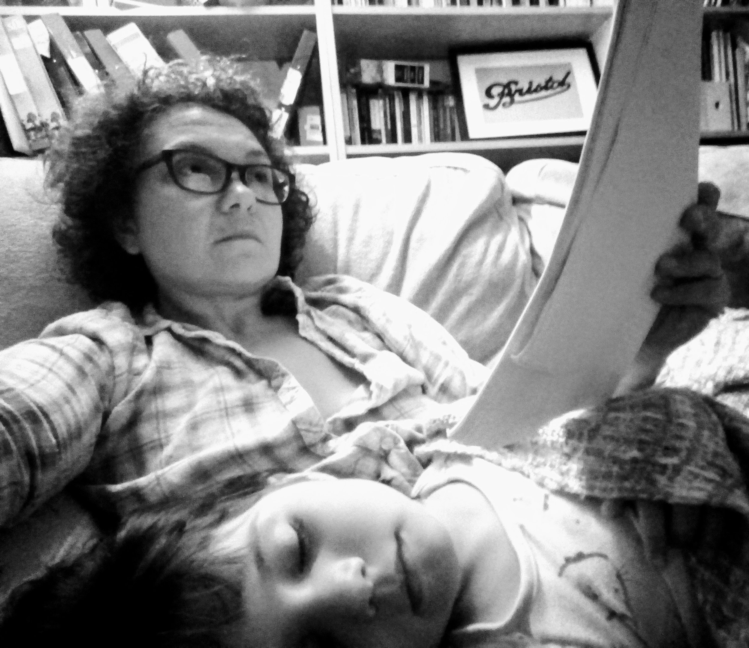 "Gill Simmons learning lines with daughter Meg asleep on her lap. The piece is Wonderland ""a new storytelling show aimed at Intergenerational audiences""."