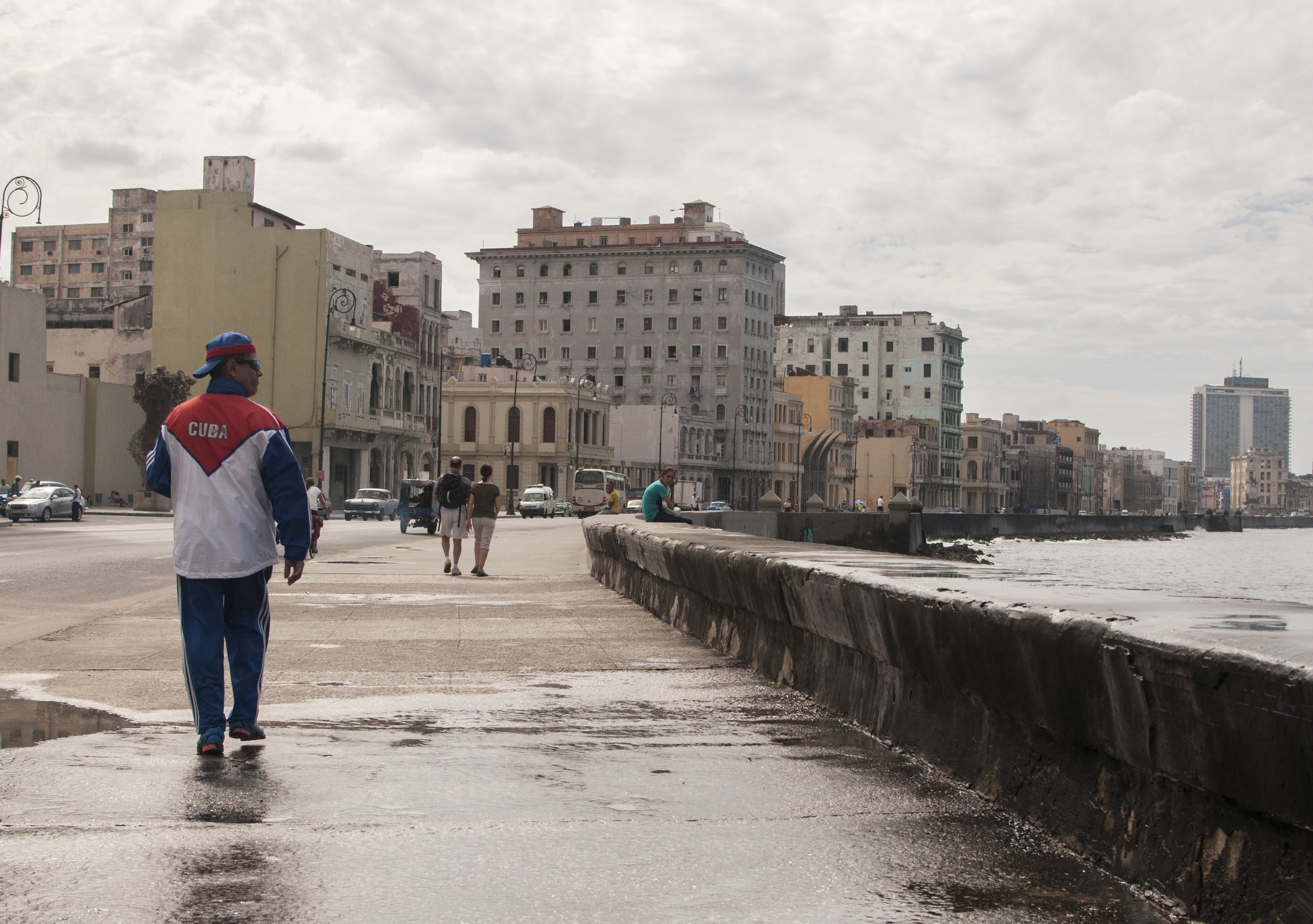 A Cuban walking along The Malecón in Havana.