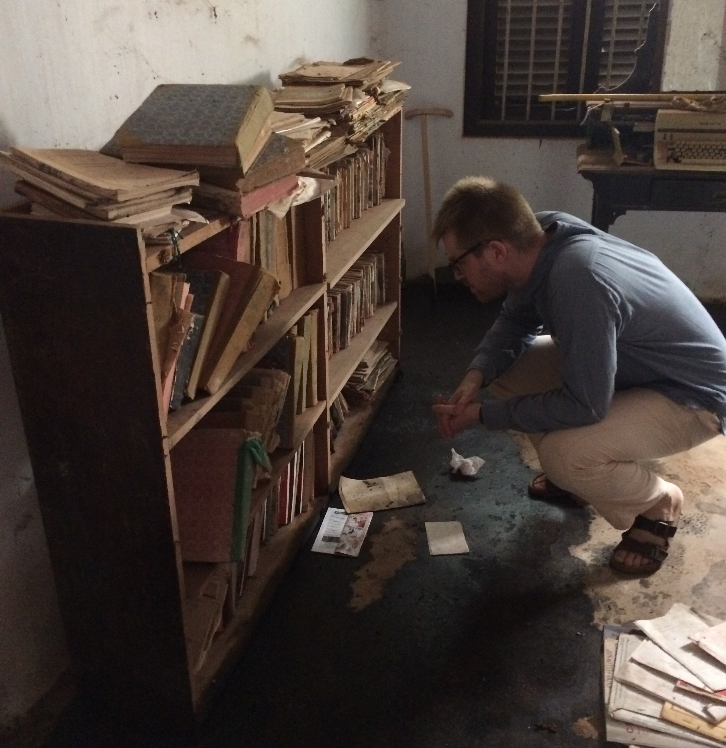 The team conducted twelve surveys of institutional and privately-held archives. The black liquid on the floor of this archive is motor oil, spread around the base of bookshelves as rudimentary protection from insects. Photo Credit: Henria Aton