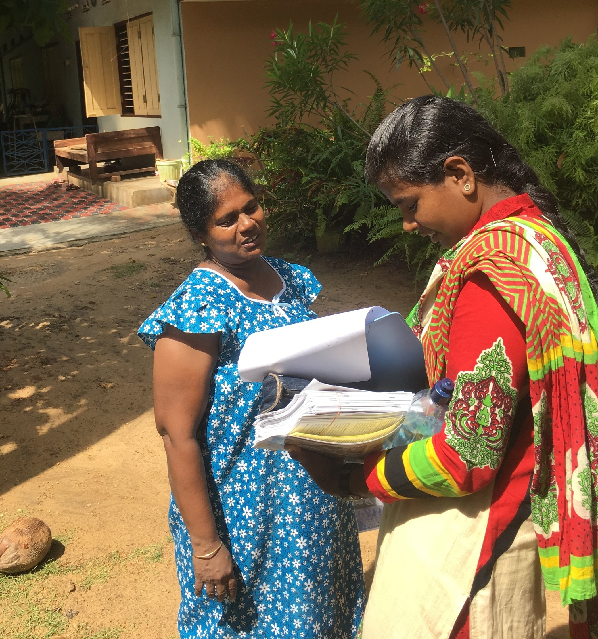 Intern Luxsana Balakumaran (right) distributing project information and participating in a door-to-door materials search campaign near St. James church. Photo Credit: Mark E. Balmforth