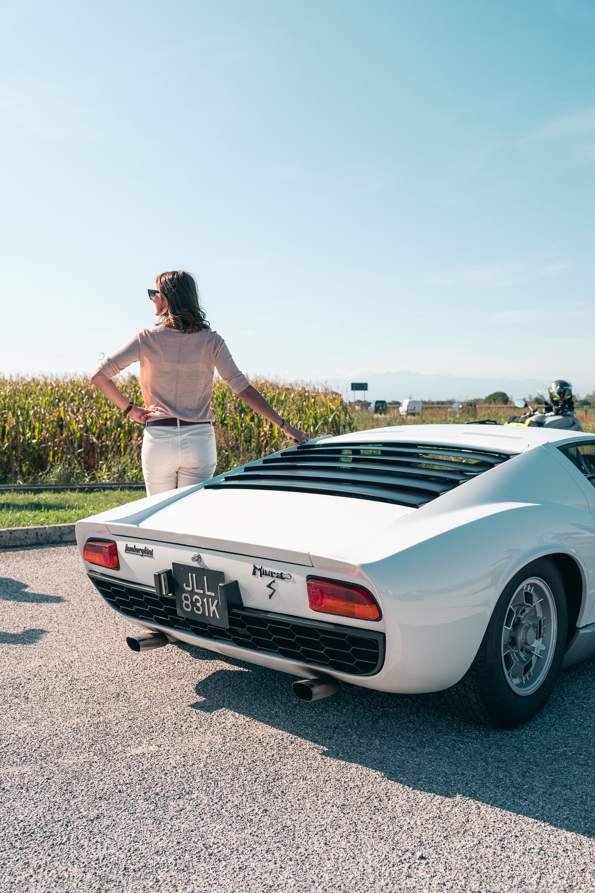 Guest poses with the splendid white Miura, best in her category.