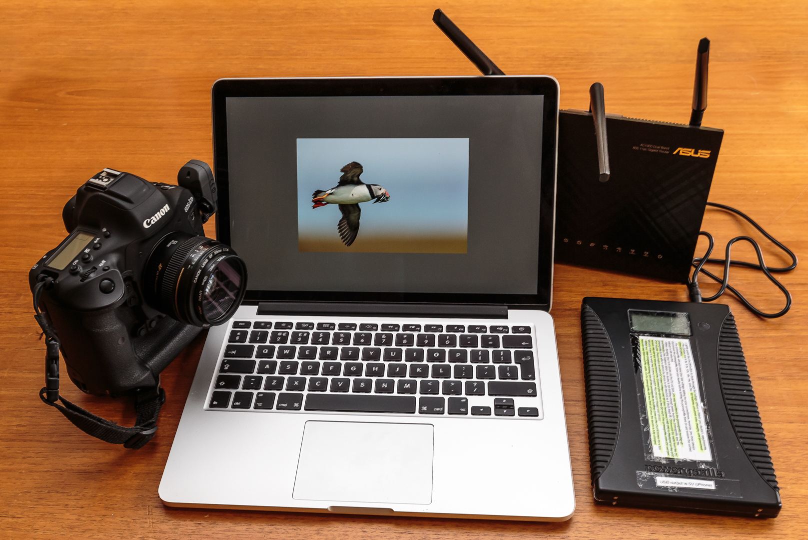 Canon camera with WFT, a laptop and a router with an attached  Powergorilla  battery for wireless file transmission using an infrastructure network.