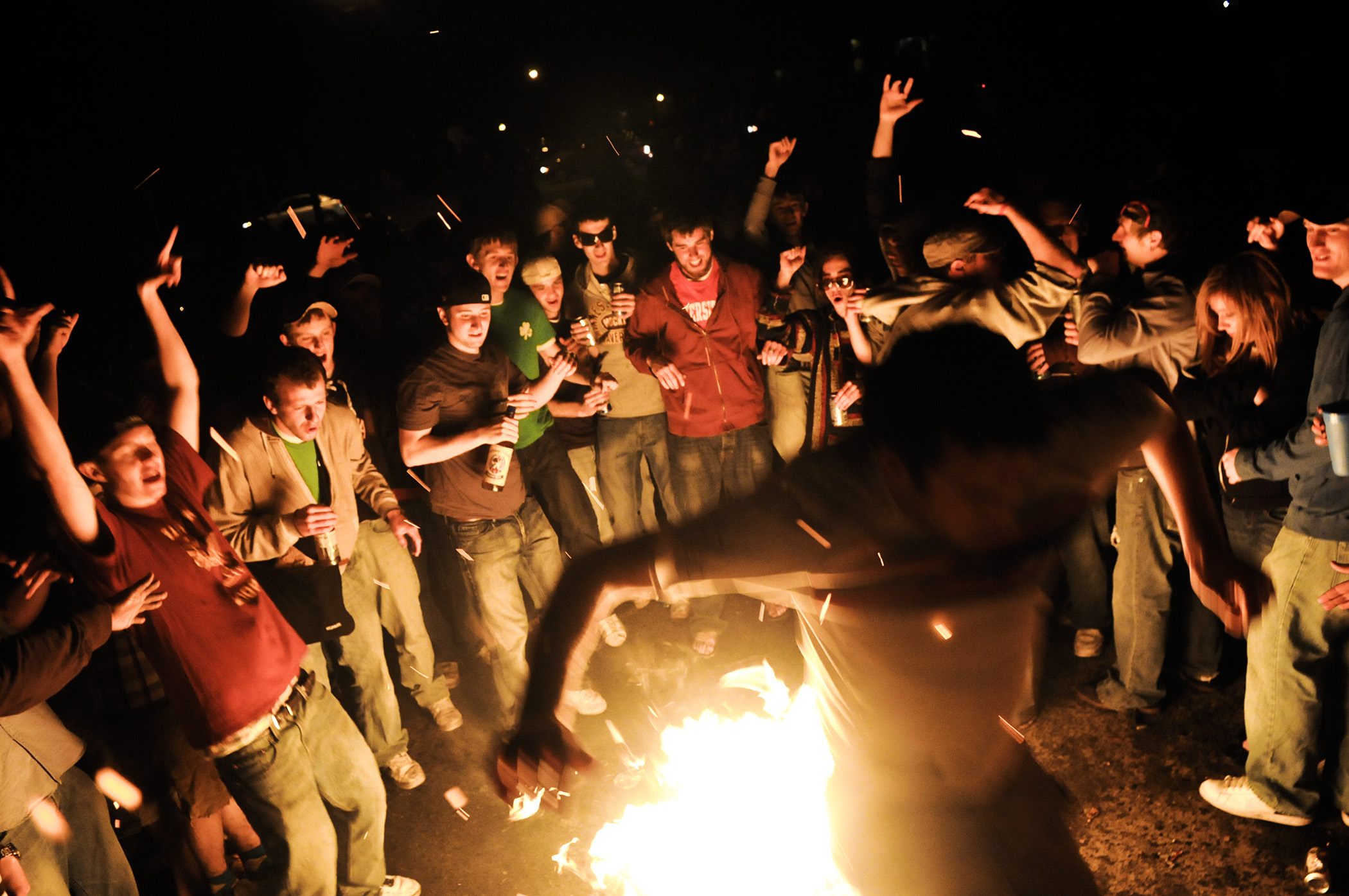 """University of Minnesota students dance around a fire set in the middle of the street during the """"Dinkytown Riots"""" on April 25, 2009 in Minneapolis, MN. The riot broke out during the school's Spring Jam celebration, resulting in the Minneapolis Police Department using teargas and pepper spray to disperse the crowds."""