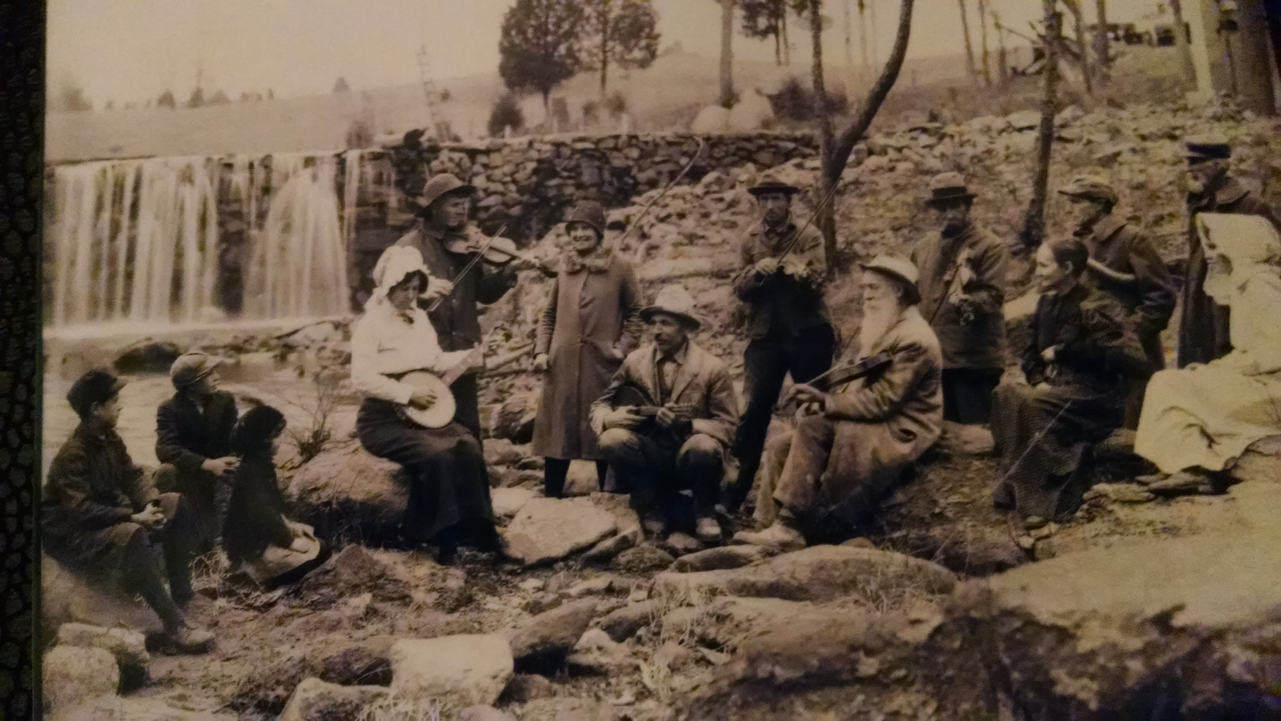 A picture of Carol's Grandmother (banjo) and Grandfather (fiddle) playing music down by the old mill.