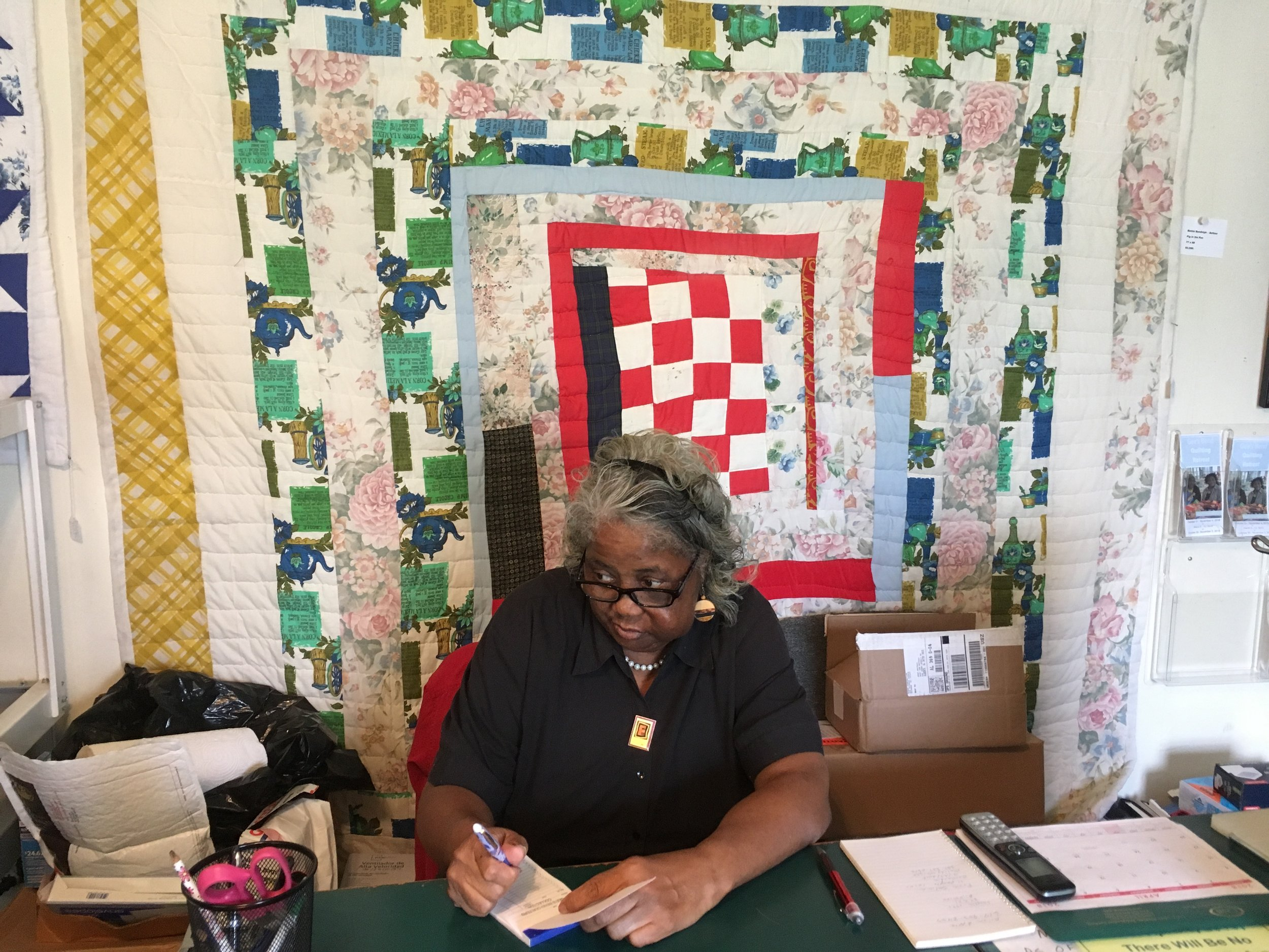 Mary Ann Pettway, Director of the Gee's Bend Quilt Collective. Sitting in front of a quilt made by Bettie Bendolph-Seltzer.