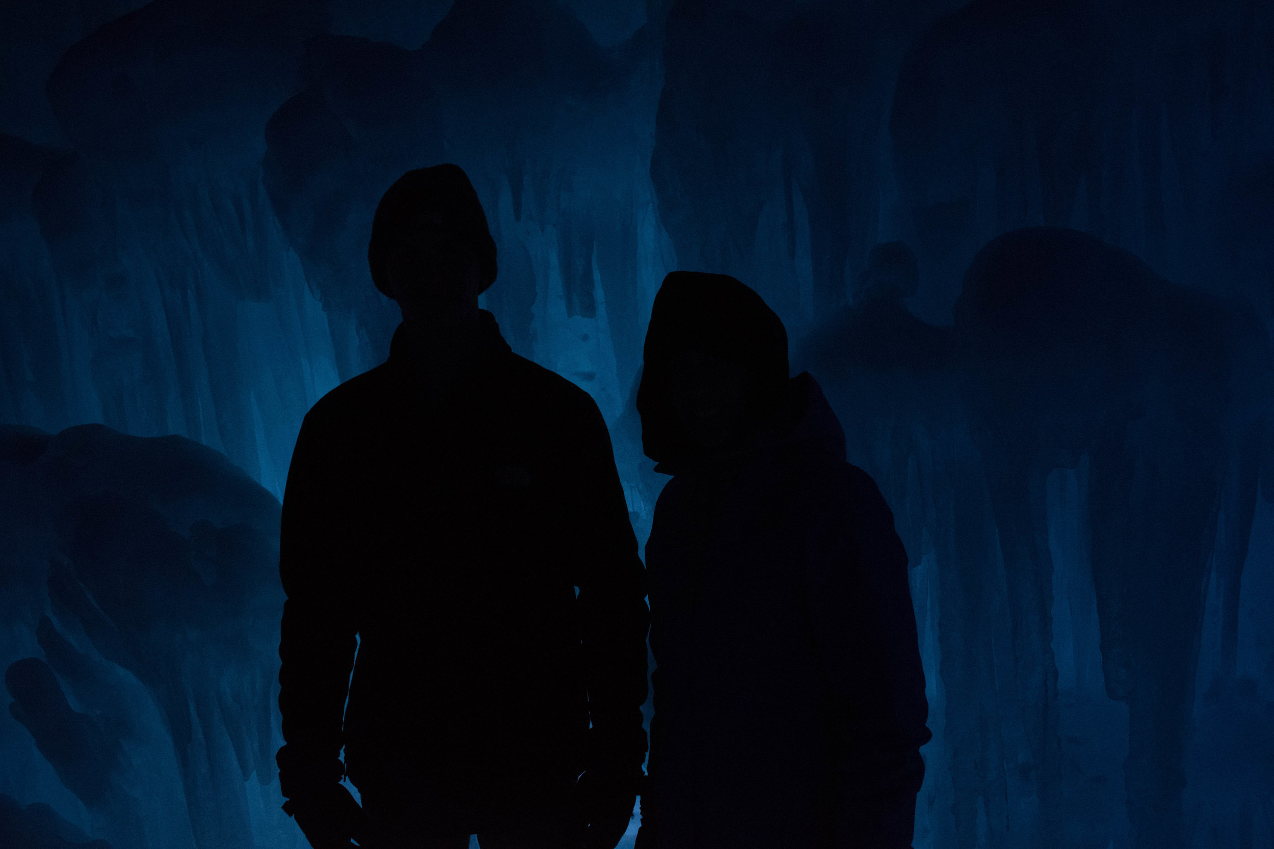 Race - Photo by Jack Michuad on Unsplash. [IMAGE DESCRIPTION: two silhouettes are seen from waist up wearing what appears to be a hoodie and the other wearing a hat on the left. The background is a dark blue cave with ice.]