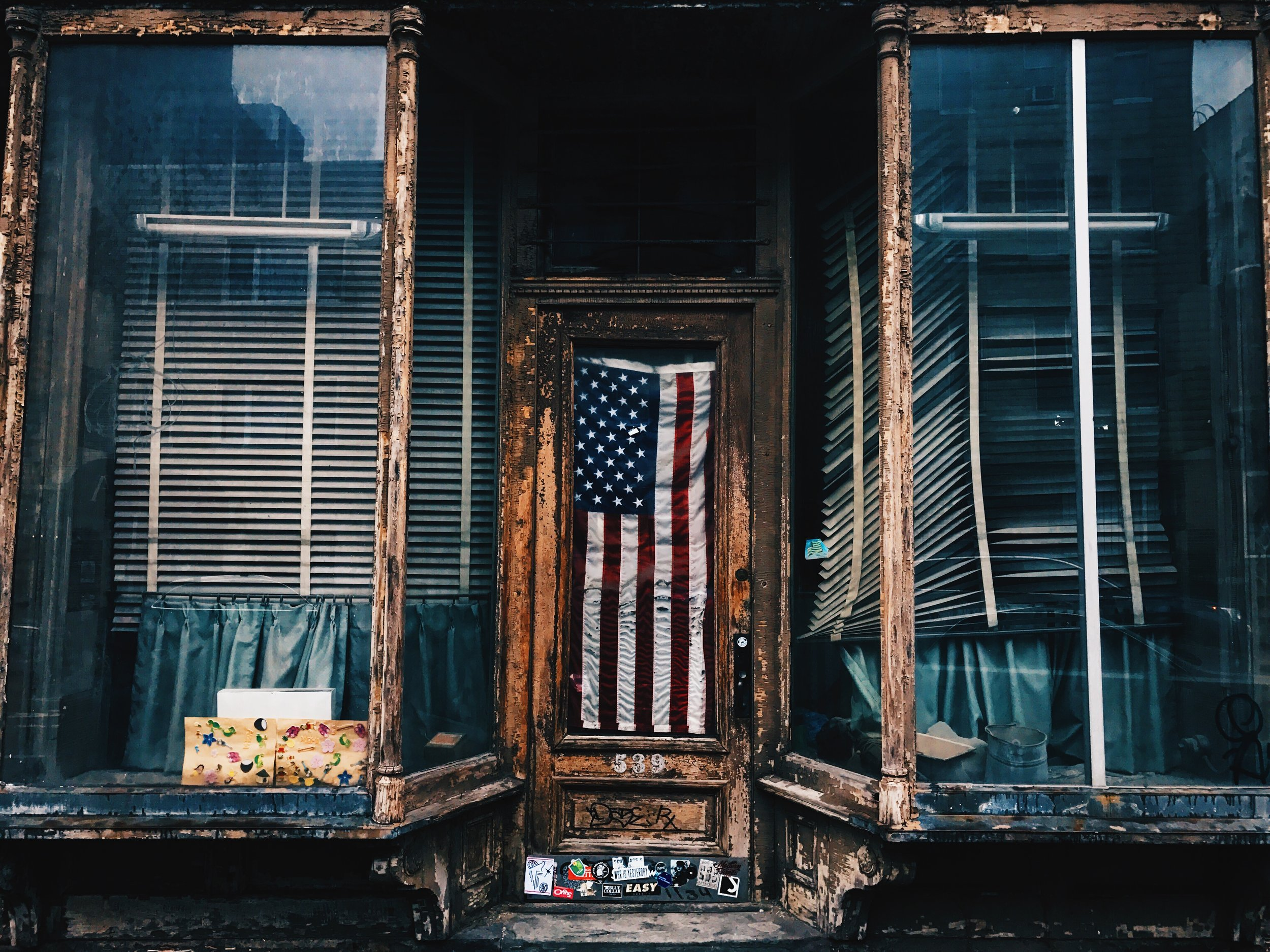 Political - Photo by Patrick Tomasso on Unsplash. [IMAGE DESCRIPTION: outside of an old rustic building, an old America flay is hung in the window of a door in the middle of display windows on the left and right.]