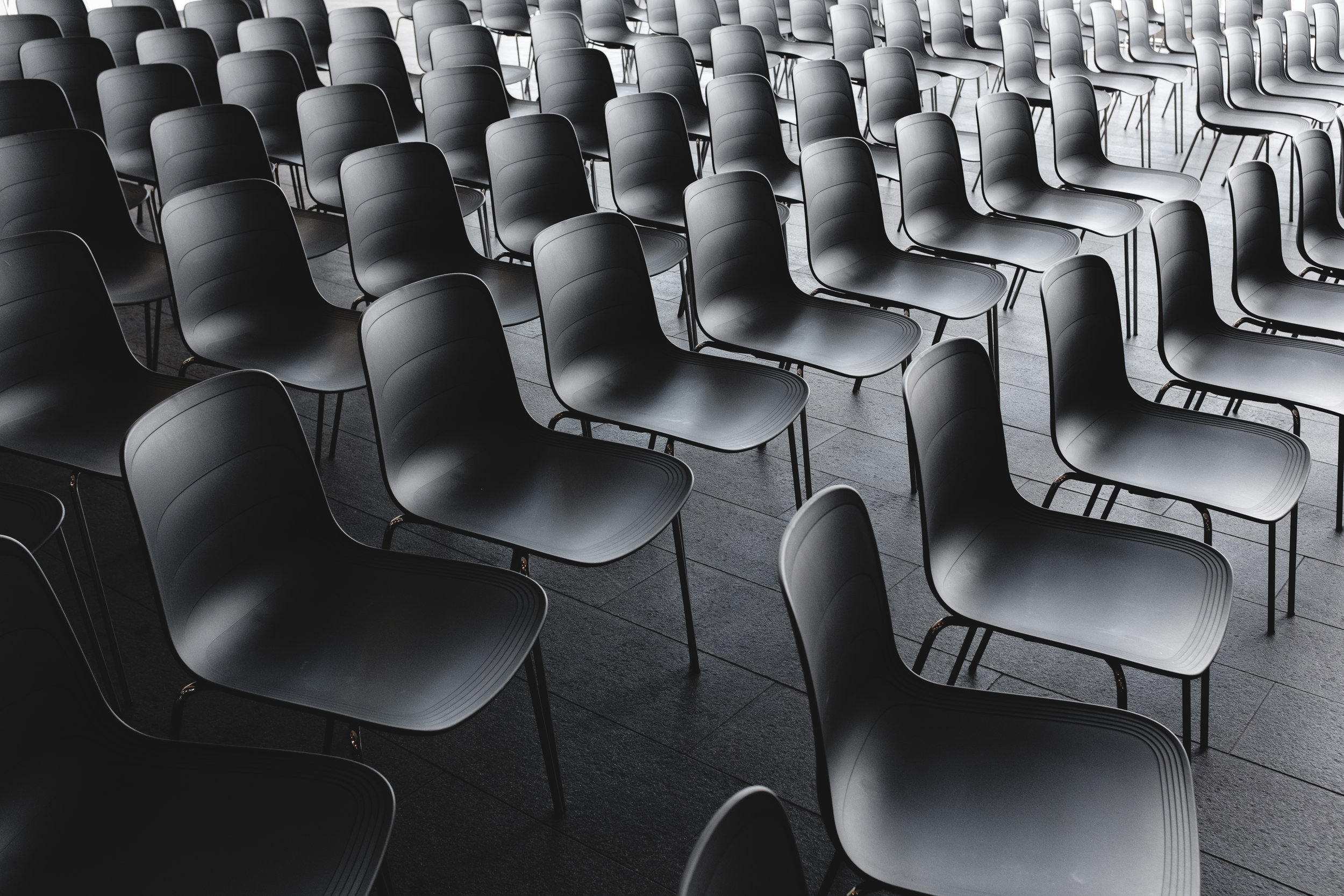 Education - Photo by Jonas Jacobsson on Unsplash. [IMAGE DESCRIPTION: the photo is black and white and the only contents of the image of rows of empty chairs that are organized what appears to be an auditorium.]