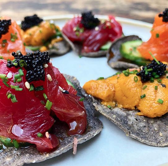 Tuna, uni and salmon over algae and blue corn tostada. Photo IG @campobaja