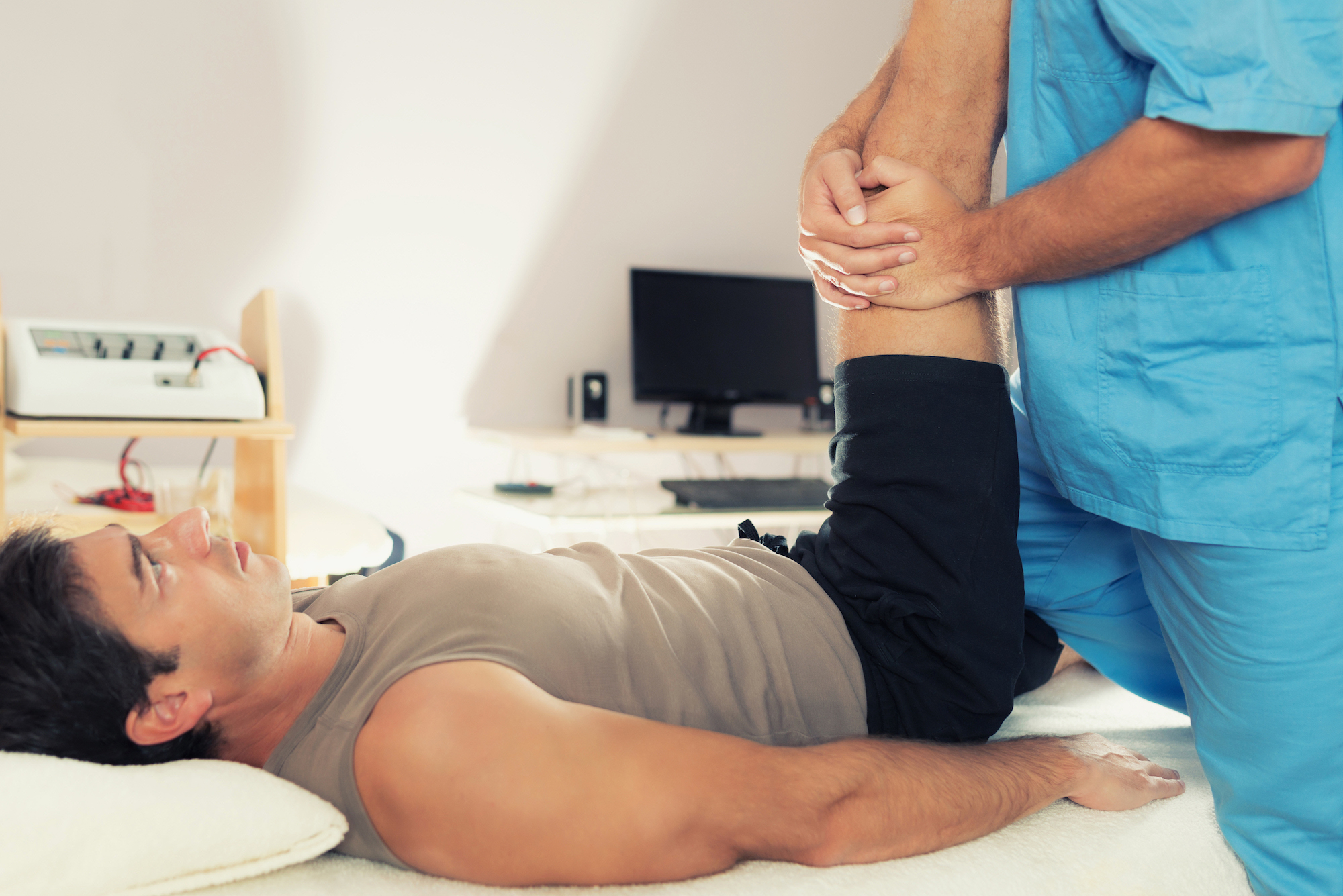 physiotherapist-working-with-patient-leg-PL4WCEX.jpg