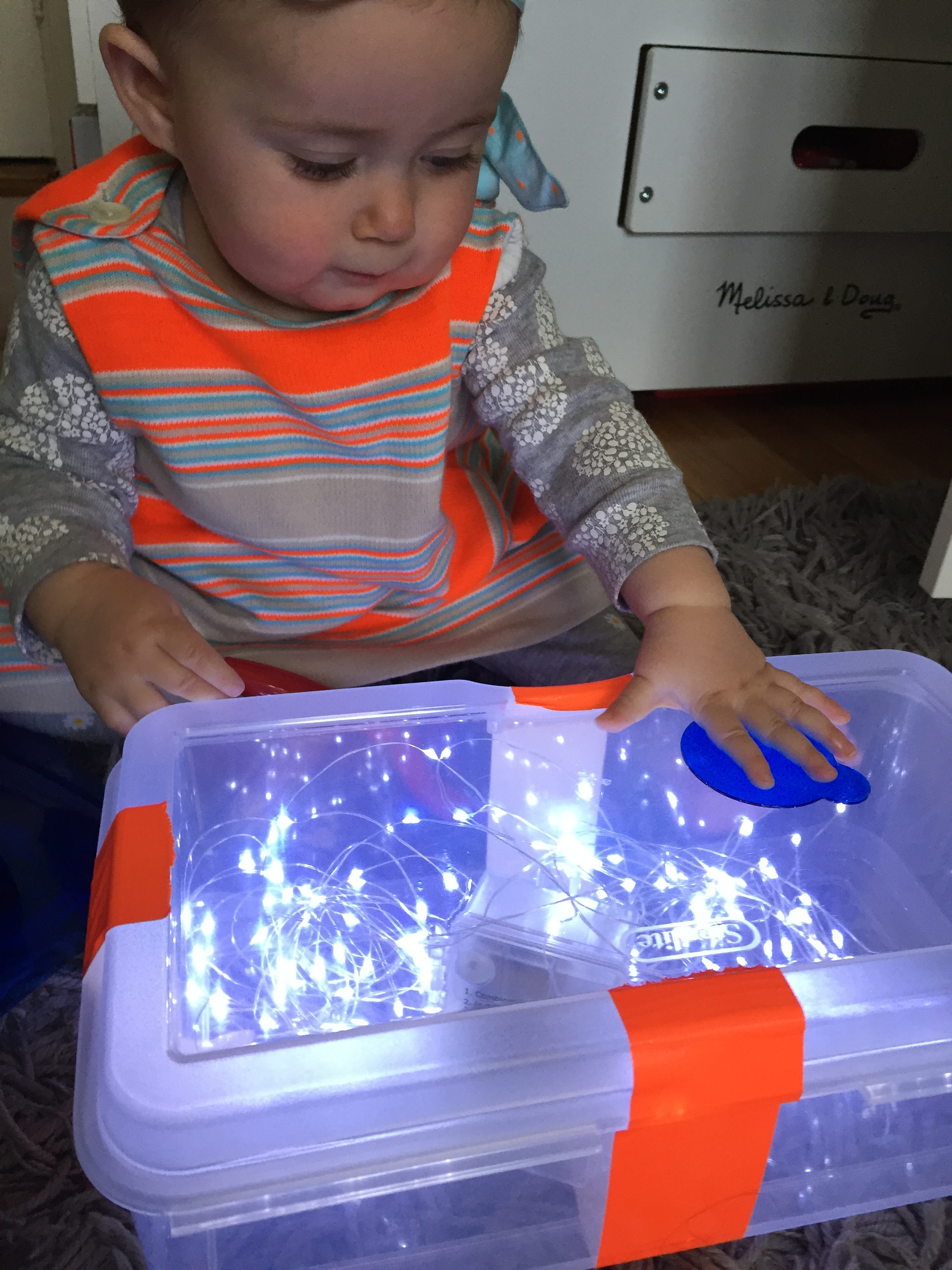 DIY LIGHT TABLE  Materials: clear box,  battery LED lights , duct tape, clear colored cellophane, magna tiles, translucent objects.  Process: Let children explore the light table. Encourage them to stack different translucent objects on the light table.  Words: light, dark, transparent, translucent, color words, shape words  Questions: What do you think will happen if? What do you see? What do you notice? I wonder…?