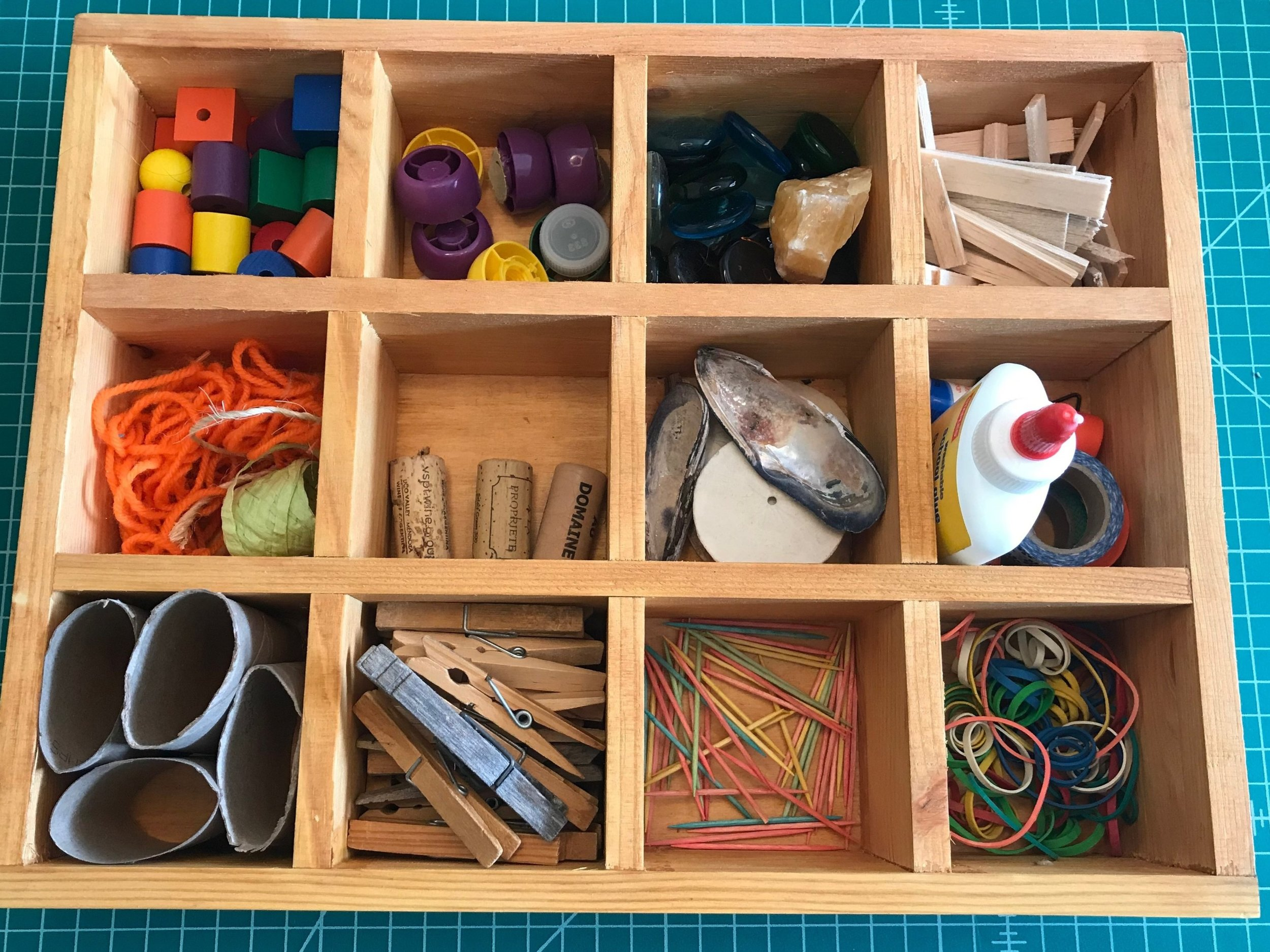 TINKER TRAY  Materials: assorted loose parts such as corks, shells, string, toilet rolls, toothpicks, and shells; fasteners like glue, tape or string. Store them in a sectional tray or  shadow box with compartments (pictured).   Process: Let children explore the materials. Discuss ideas for what you may want to create. For children 4 and up, try drawing a picture of your ideas first, or after they are done. Always supervise when children are using glue gun and/or scissors. Use with other materials such as cardboard, wood pieces, play-dough and more!  Words: build, fasten, texture, strong, balance, color words, shape words  Questions: What do you think will happen if? What did you make? What does it do? What is it called?