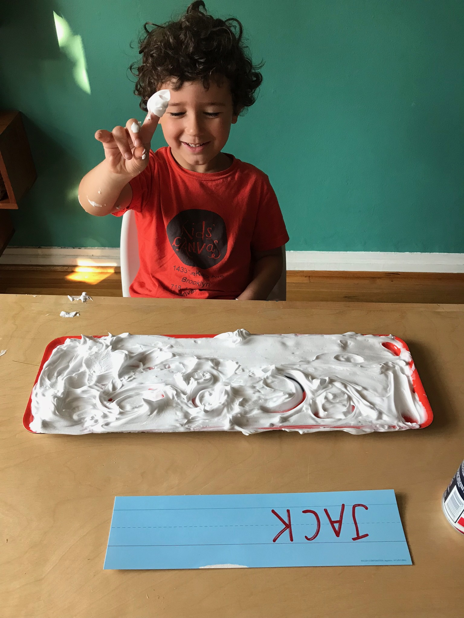 SHAVING CREAM  Materials: Shaving cream, low baking sheet or tray  Process: Allow children to explore the texture and feel of the shaving cream and encourage them to create shapes with their fingers. Older children can practice writing their name, which helps them form letters in later writing.  Words: ABC's, push, squiggle, stretch, shape words  Questions: What can you make? What did you try? I wonder if?
