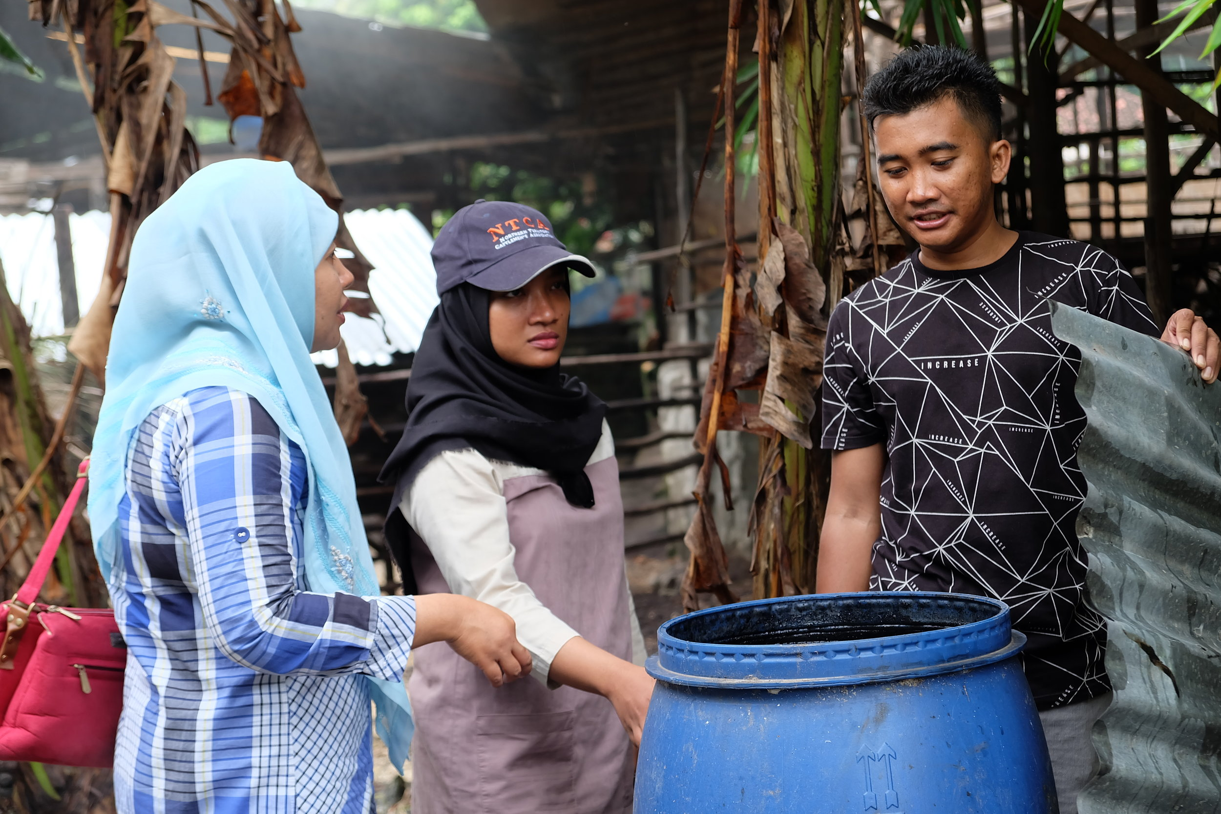 Dr Yenny Nur Angraenny and Febrina Prameswari discuss a liquid smoke trial to protect plants and animals against insects with group leader Pak Suwandi.