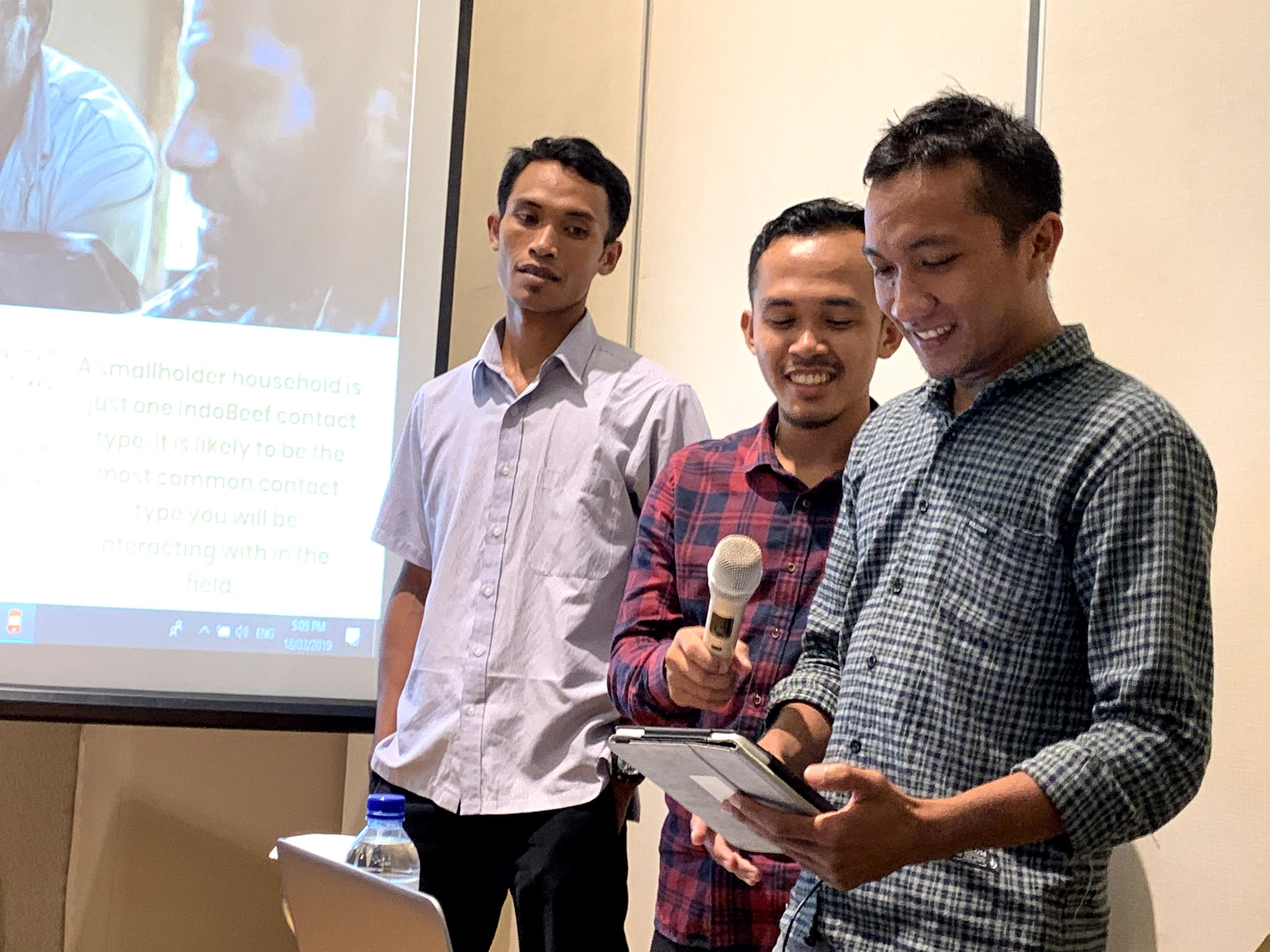 IndoBeef Field Officers Sukri, Adis and Fauzan demonstrate the steps taken to register a smallholder farmer in the IndoBeef CommCare application during a role-play activity.  Photo: Michael Halliday
