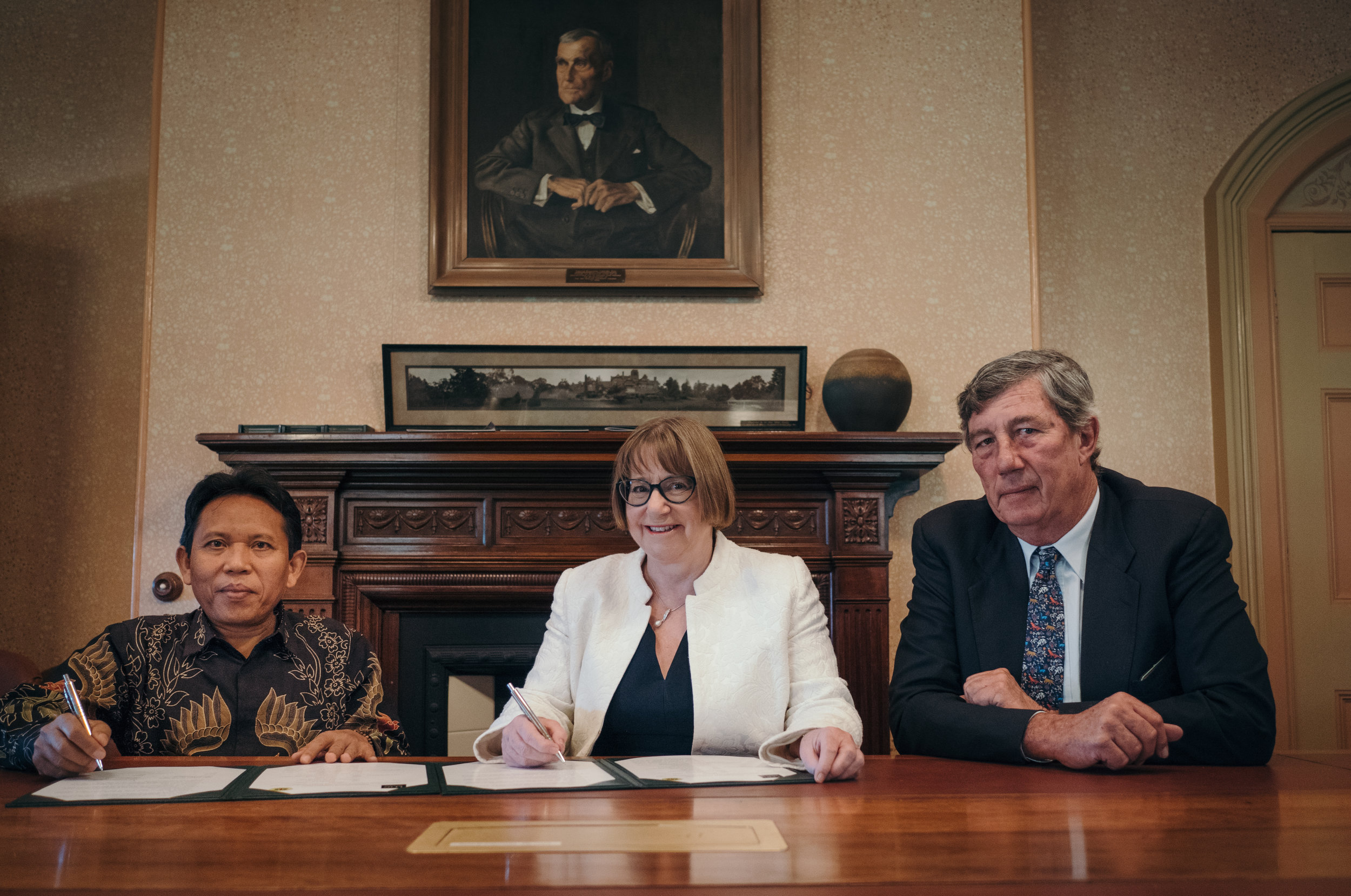 Rector of the University of Mataram, Professor Lalu Husni, signs the MoU with UNE Vice-chancellor, Professor Annabelle Duncan, and Chancellor James Harris.  Photo: Matthew Cawood
