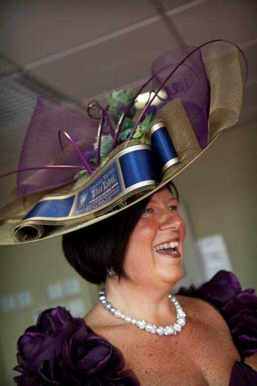 "Janice Withers   ""I have attached a photo of my hat. I hope you can see by my face how much I enjoyed wearing it. Ascot was a blast and your design was photographed and spoke about to death. The picture I have sent was taken at the final event of Diageo Kilmarnock where I was asked to wear my hat to show my passion for Johnnie Walker."""