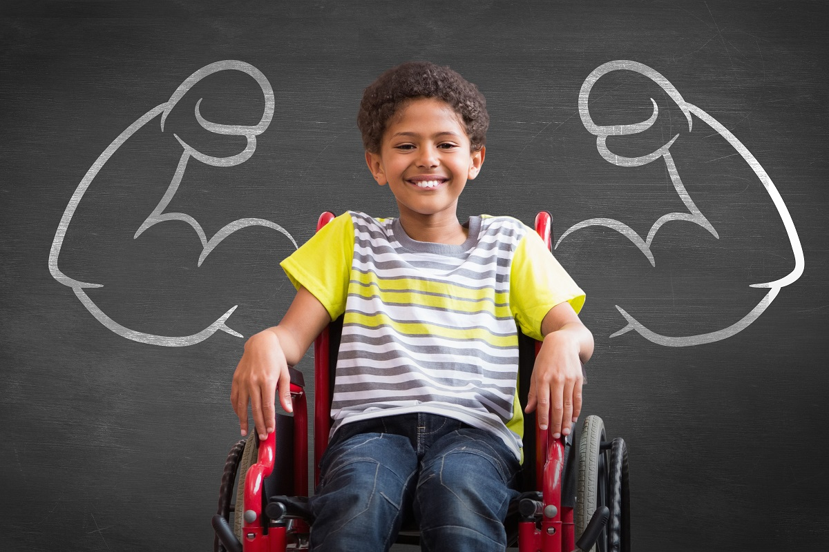 Photo Caption: Image of a young boy in wheelchair smiling. He sits in front of a chalkboard image with large muscular arms drawn behind him, made to look like they were his own.