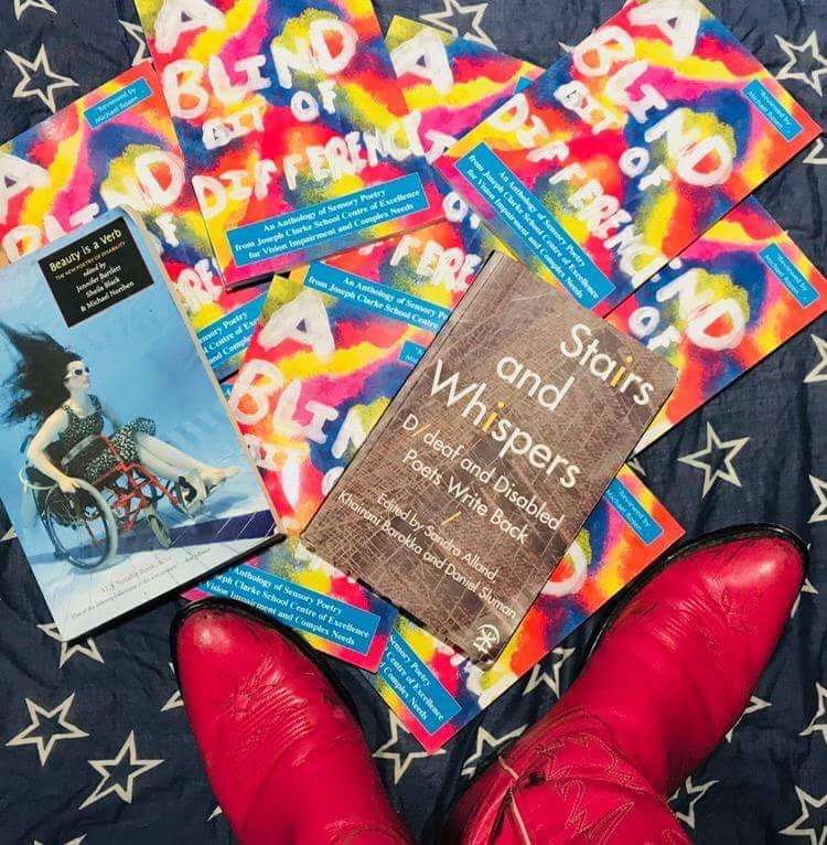 """Multiple vibrant copies of the A Blind Bit of Difference book are laid out haphazardly on a black and white star covered scarf. Two other books are pictured in the image, """"Stairs and Whispers"""" and """"Beauty is a verb"""". The photographer's bright pink cowboy boots are in the bottom of the picture"""