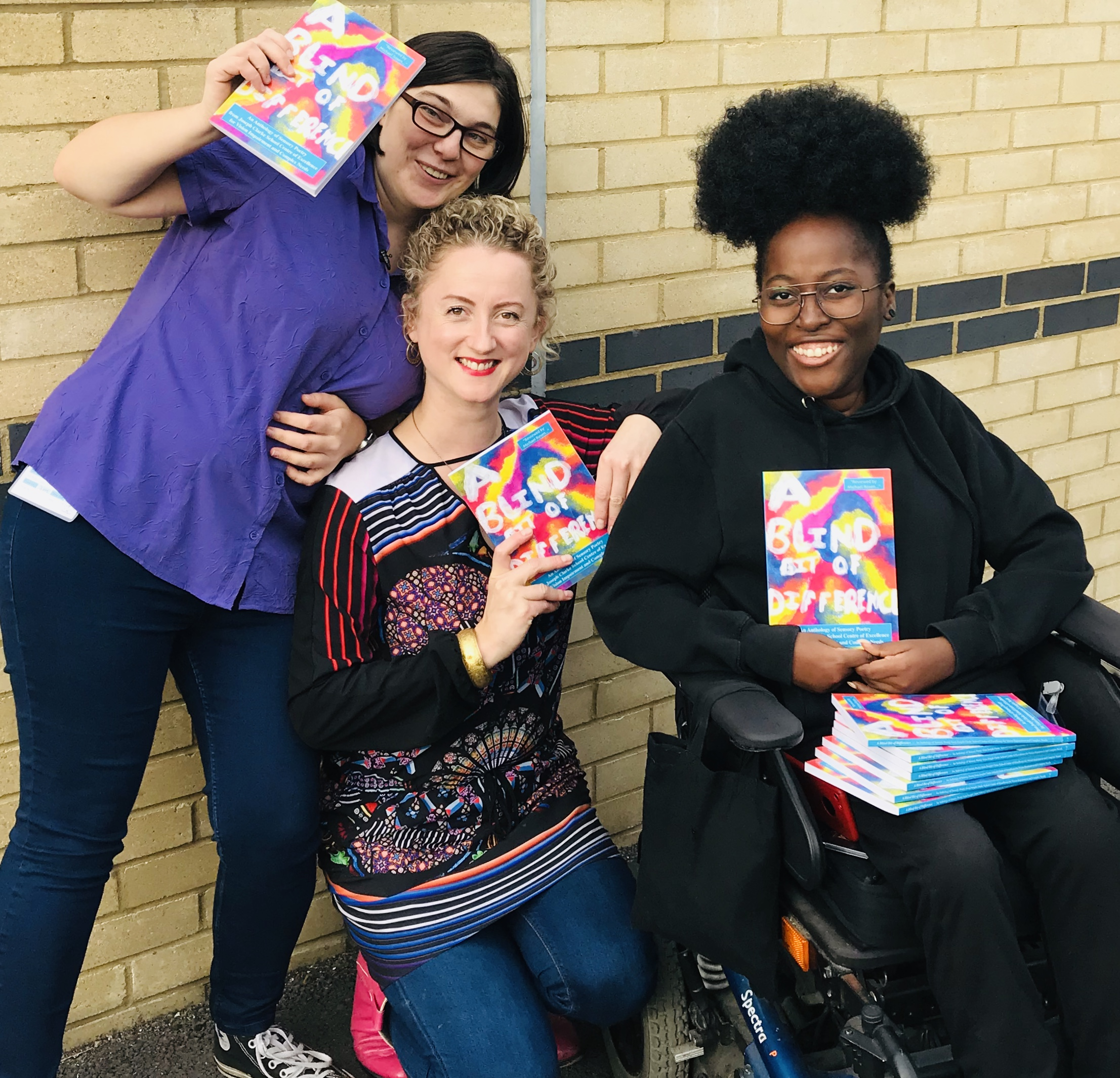 Image Description: photograph  of featured artist Zara Jayne, Project manager Amy Neilson Smith and proud wheelchair user and artist Miss Jaqui pose with copies of A Blind Bit of Difference in front of a beige wall