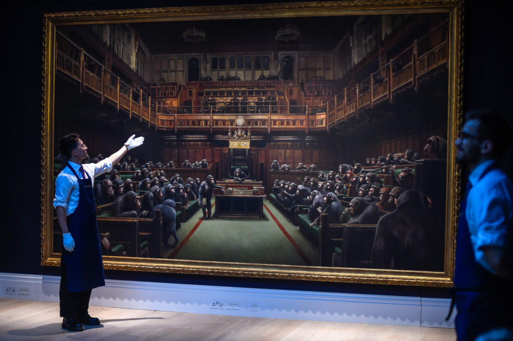 Gallery workers display Banksy's 'Devolved Parliament' prior to a photo call at Sotheby's on September 27, 2019 in London, England. Photo by Peter Summers/Getty Images.