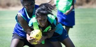 High school girls enjoying their day of football as Sophira Buaneye tackles Tia Sampi