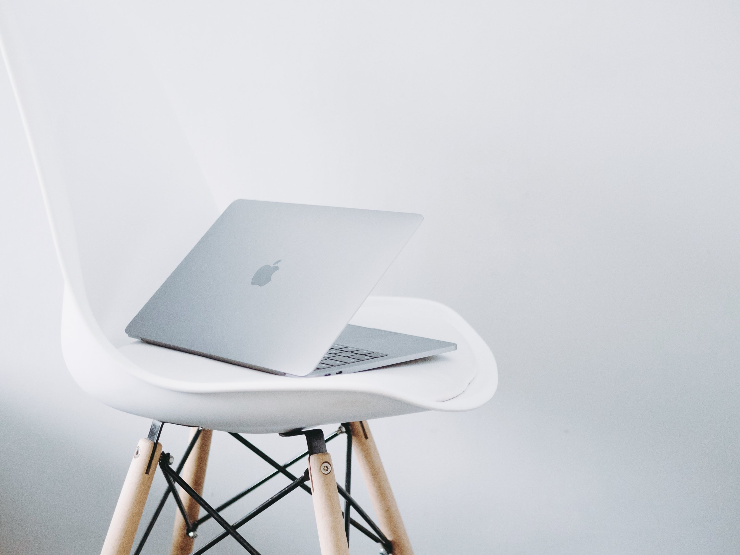Apple MacBook on a white stool