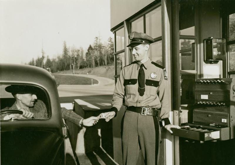A cheerful toll collector greets a driver heading across Mercer Island to Seattle in 1940.