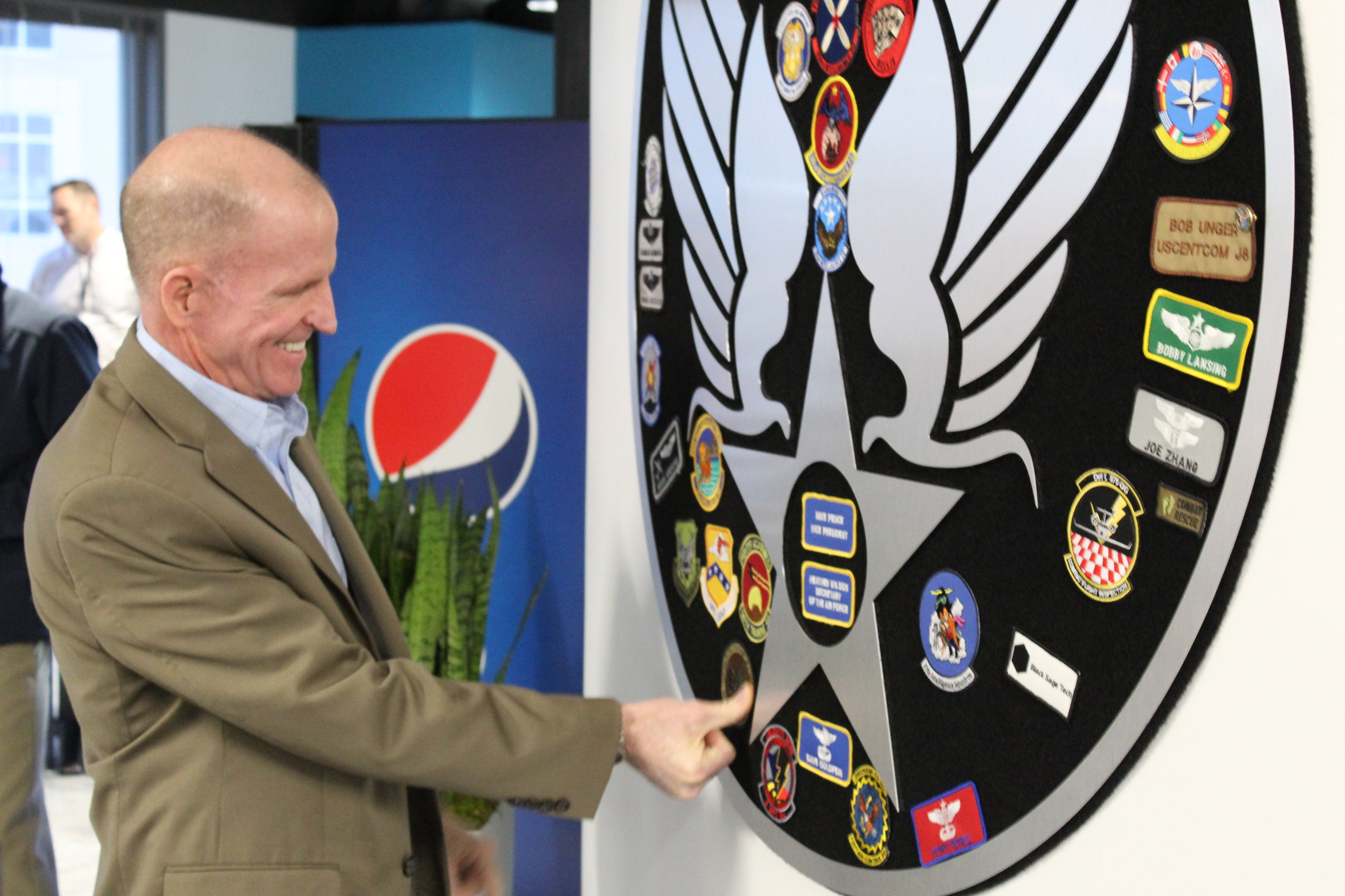 "Vice Chief of the Air Force Gen. Stephen W. ""Seve"" Wilson adds his insignia to the ""patch wall"" at the AFWERX Vegas Innovation Hub. Wilson and other senior Air Force leaders informally met with approximately 60 airmen and AFWERX personnel, launching a 4-day facilitated workshop. Airmen were tasked with identifying opportunities for innovation in training rotary-wing, battle management, and remotely-piloted aircraft personnel."