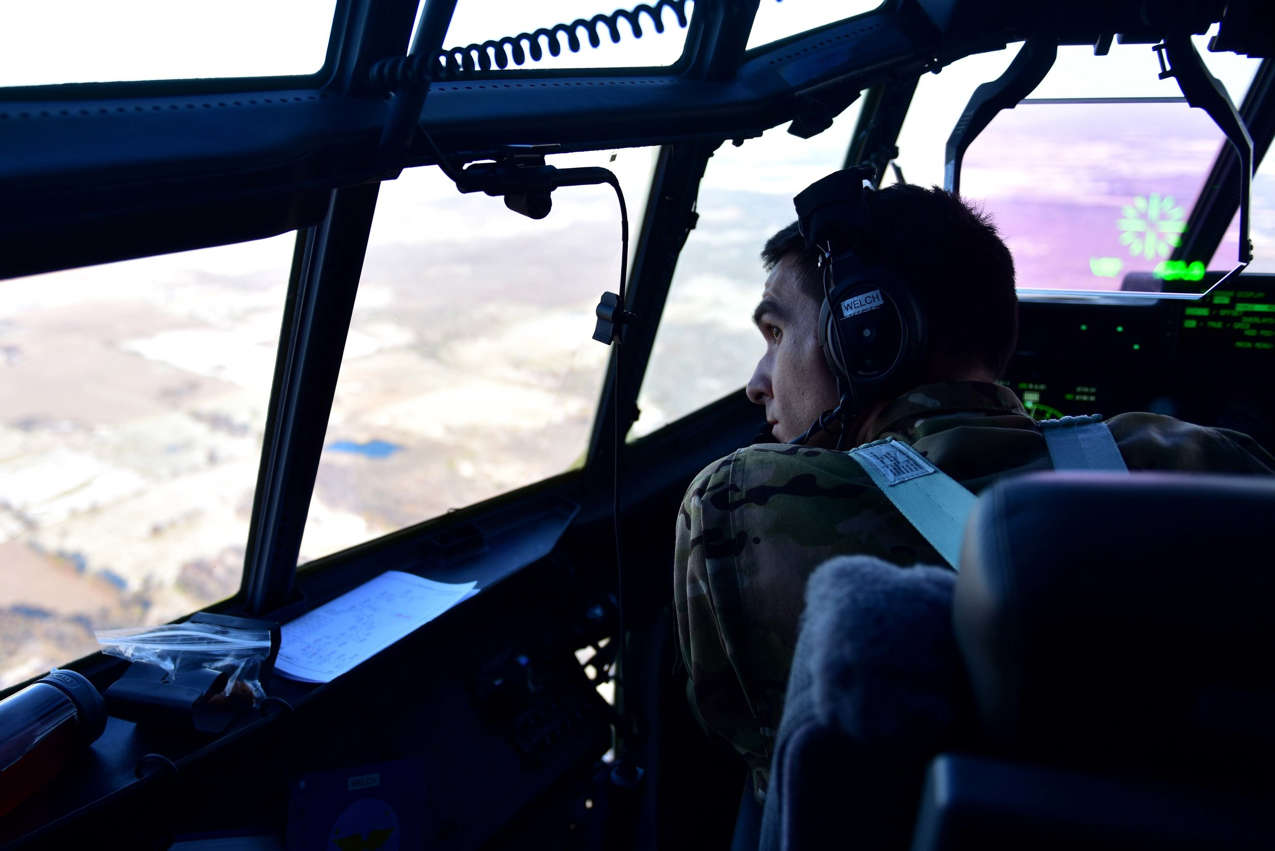 """U.S. Air Force Lt. Col. Christopher Welch, 19th Operations Support Squadron commander, looks out the window of a C-130J while flying over Little Rock Air Force Base, Ark., Nov. 14, 2018. Using Augmented Reality/Virtual Reality (AR/VR) tools, aircrew could soon be able to train on cockpit radio set-up and procedures with real-world tactical air-control personnel """"on the ground,"""" without having to take flight themselves. Photo by Airman 1st Class Kristine M. Gruwell"""