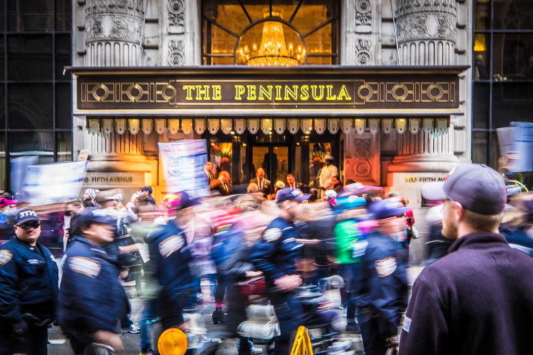 New York, NY - Jan. 21, 2017: Protesters pass by The Peninsula Hotel on 5th Ave. as part of The Women's March on NYC. The protest took place the day after the Presidential inauguration of Donald Trump and concluded at Trump Tower.